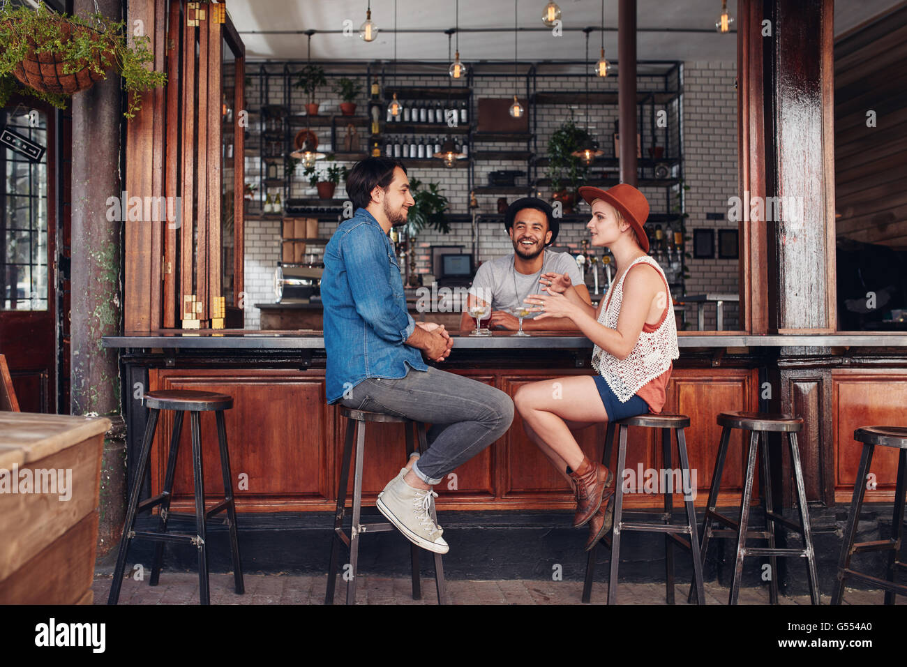 Portrait of happy group of young people meeting in a coffee shop and talking. Three young friends sitting at a cafe - Stock Image