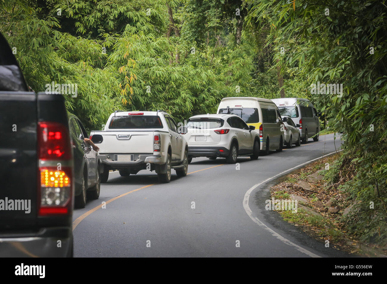 Cars, vans and pickups slow running up to mountain of green tropical forest. There is small lane of road cut inside Stock Photo
