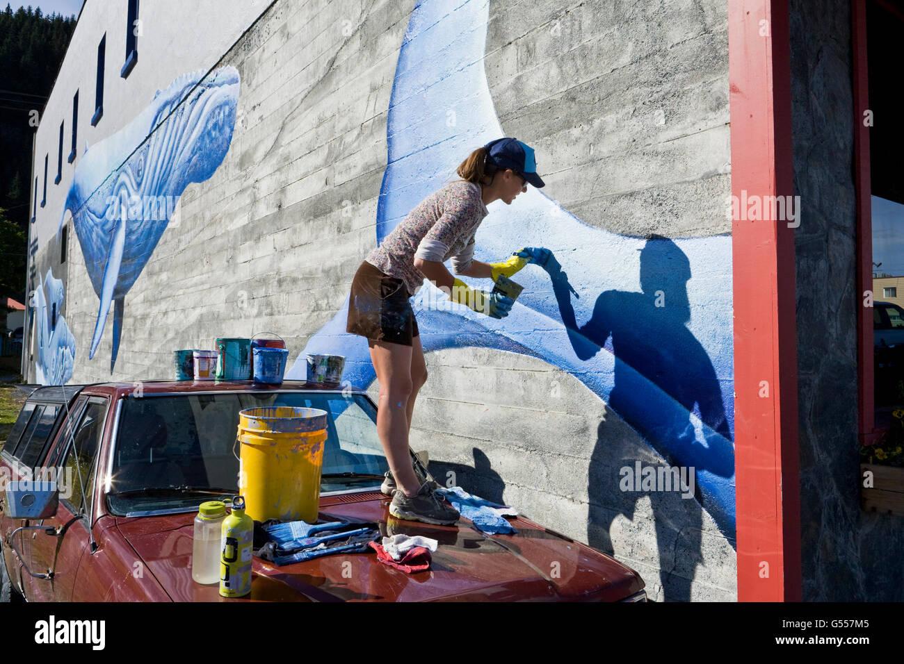 Artist Justine Pechuzal painting her mural 'Sea-ward Bound' depicting  humpback whales (Megaptera novaeangliae) - Stock Image