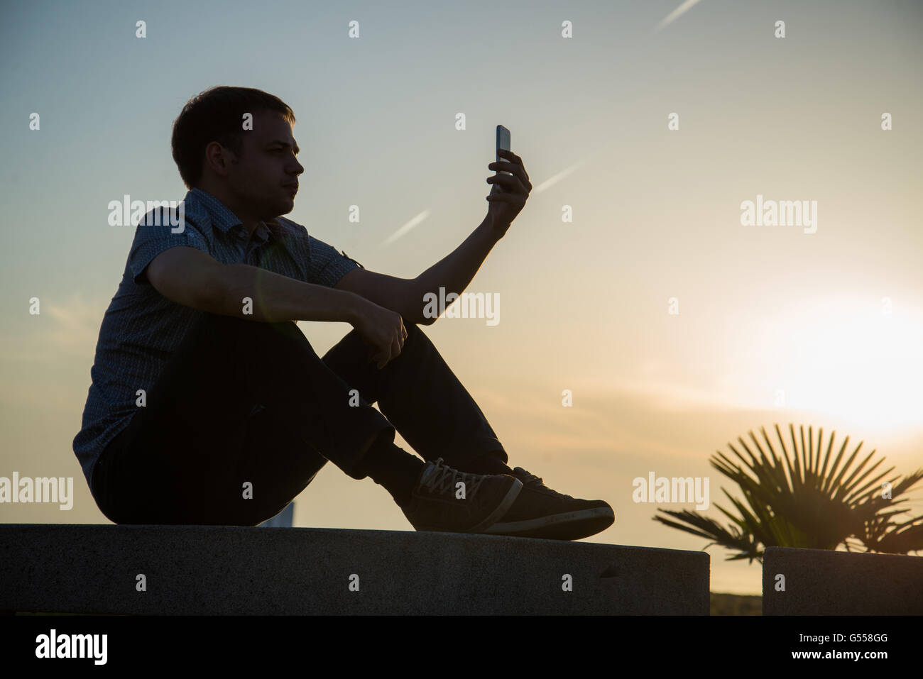 Young guy is watching photos on mobile phone what he took now during rest near sea with copy space background for - Stock Image