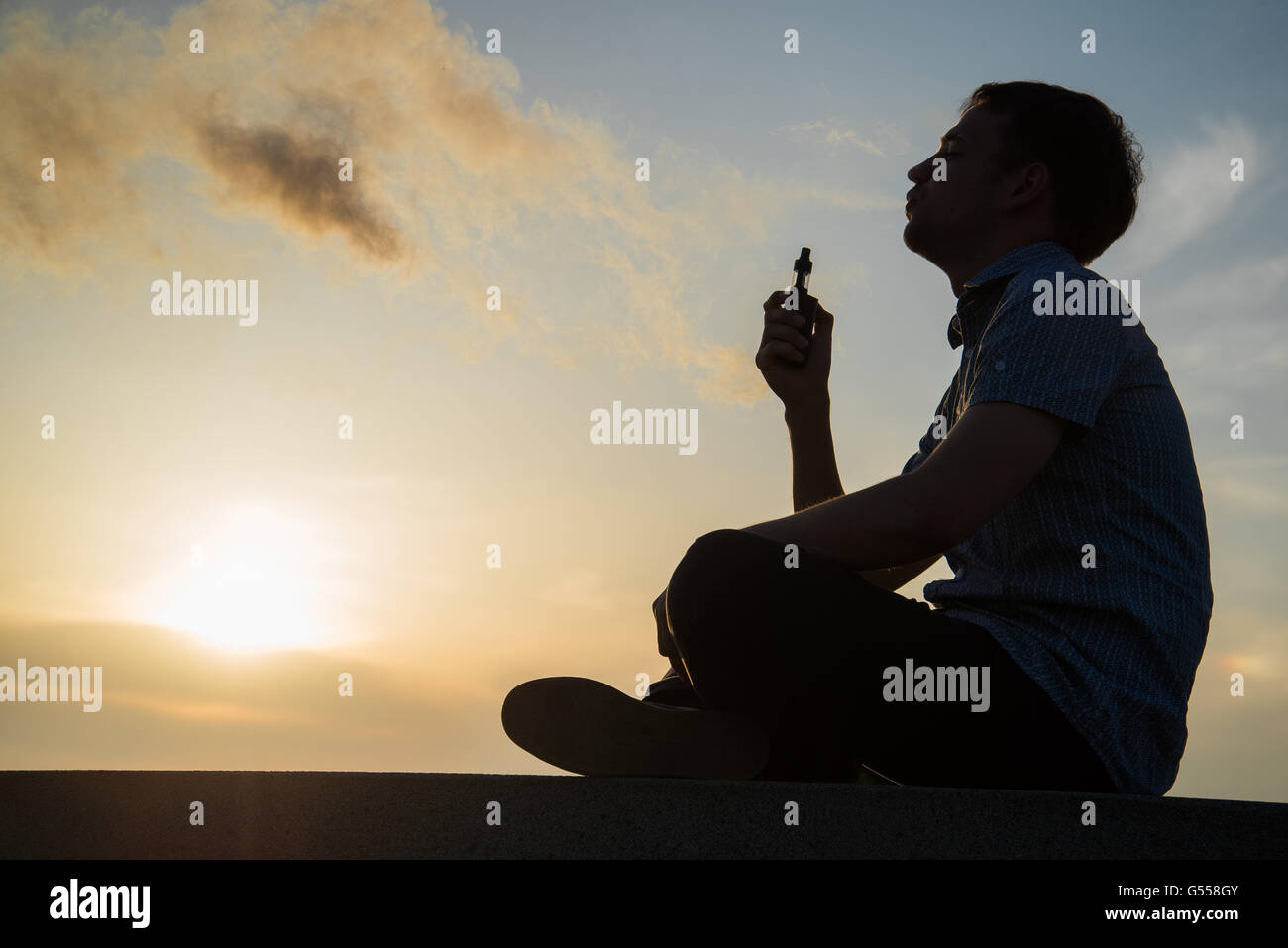 Man smoking vaping e-cigarette vape box mode over golden sunset - Stock Image