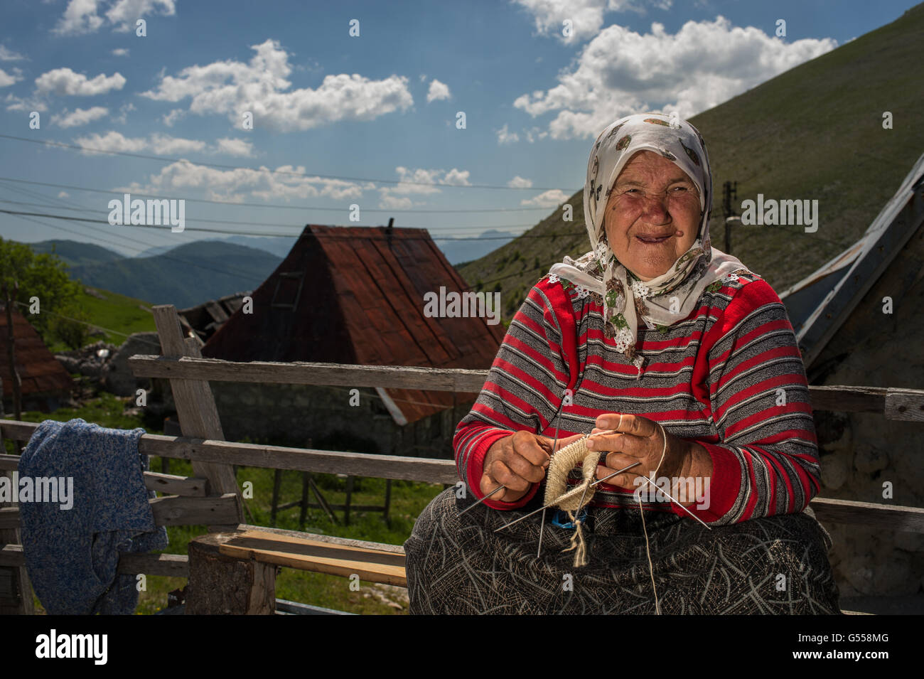 An old woman by Lukomir, the most remote and higher village of Bosnia-Erzegovina  Europe, prepare typycal wool socks. - Stock Image