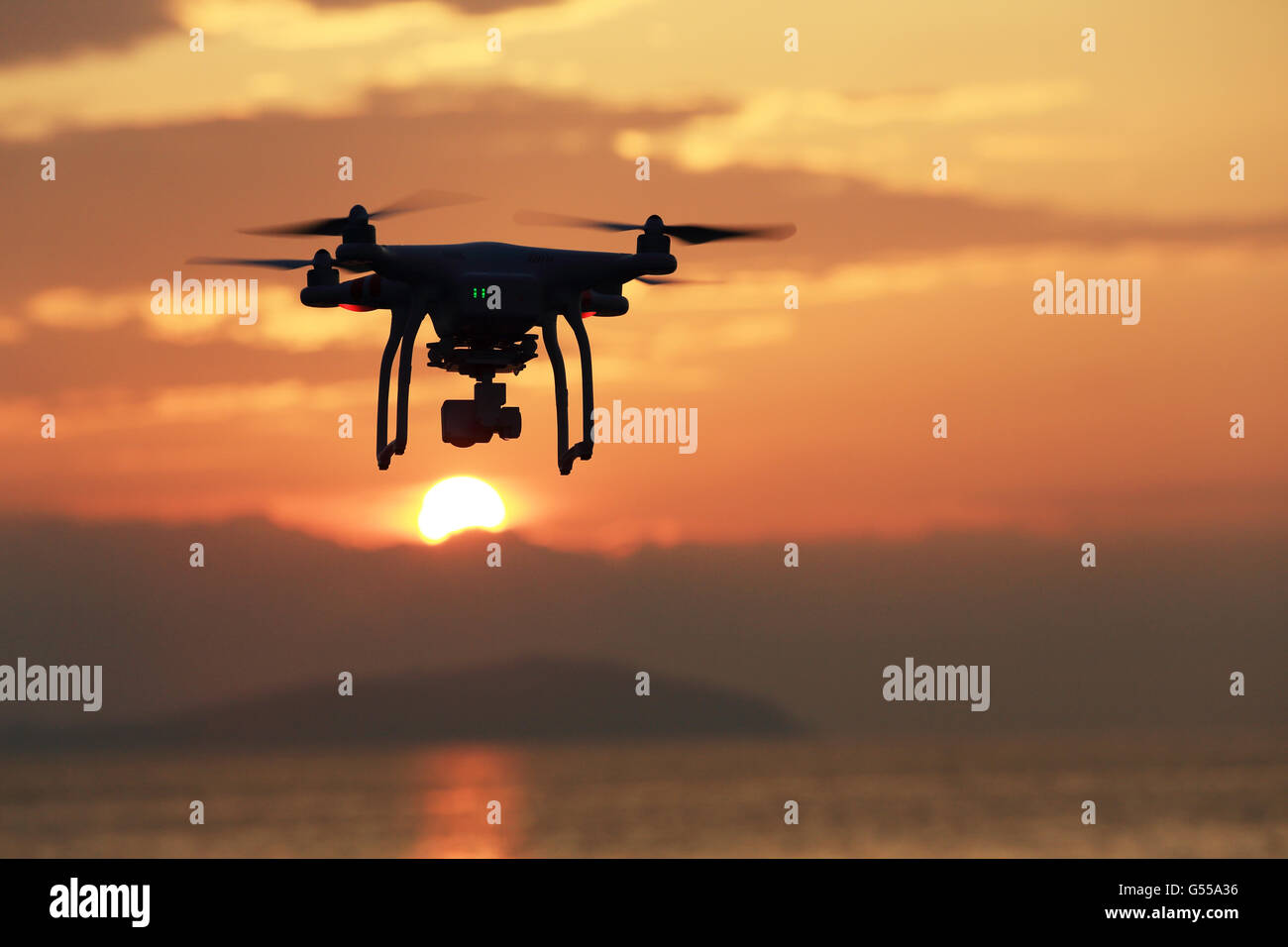 Drone flying against a sunset sky - Stock Image