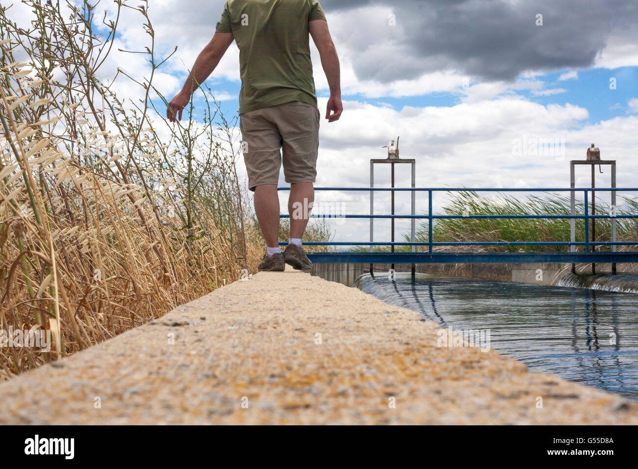 Keeper Mature man walking by huge irrigation canal of High Guadiana or Vegas Altas, Extremadura, Spain - Stock Image