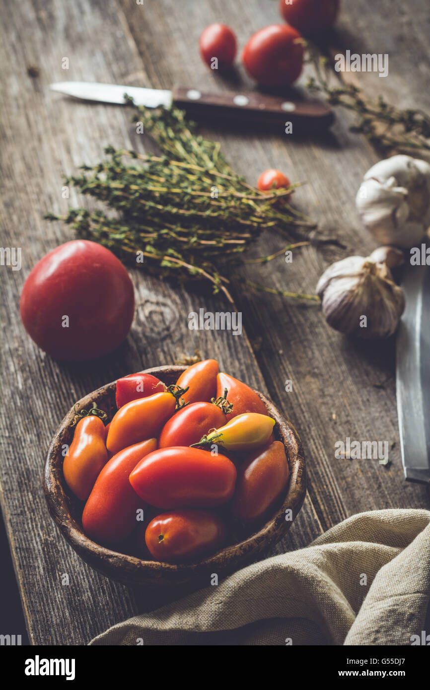 Heirloom tomatoes, banch of thyme springs, garlic and knife on rustic wooden table. Atmospheric rustic still life - Stock Image