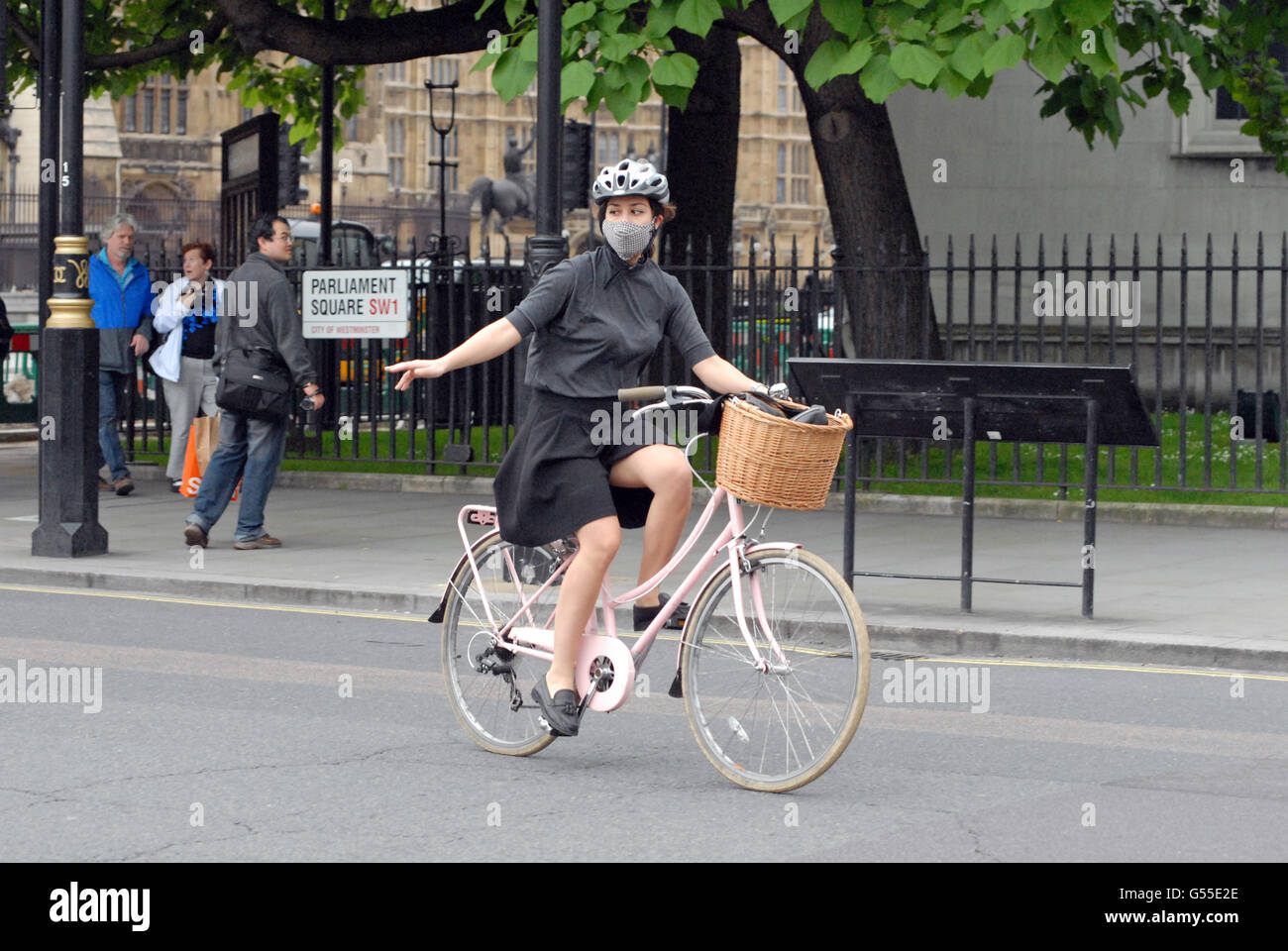London, UK, 18 June 2016, Girl cyclist with air filter mask on pink bike in Parliament Square in Central London. - Stock Image