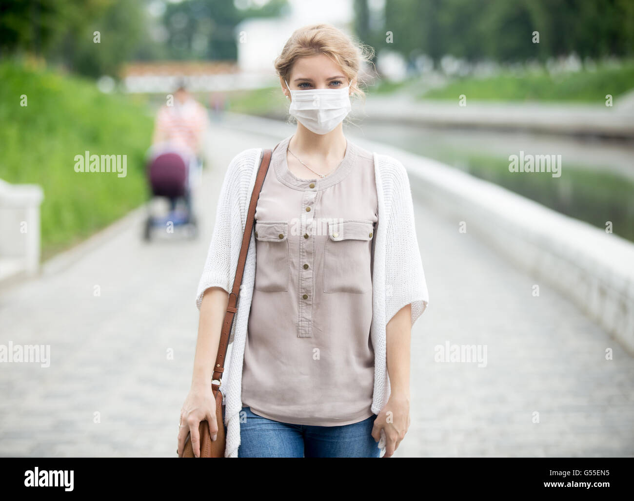 Portrait of beautiful woman walking on the street wearing protective mask as protection against infectious diseases. - Stock Image