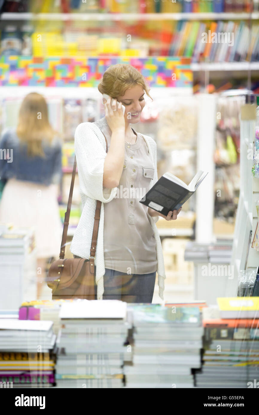 Lifestyle portrait of happy beautiful person using smartphone standing in bookstore and looking through books. Young - Stock Image