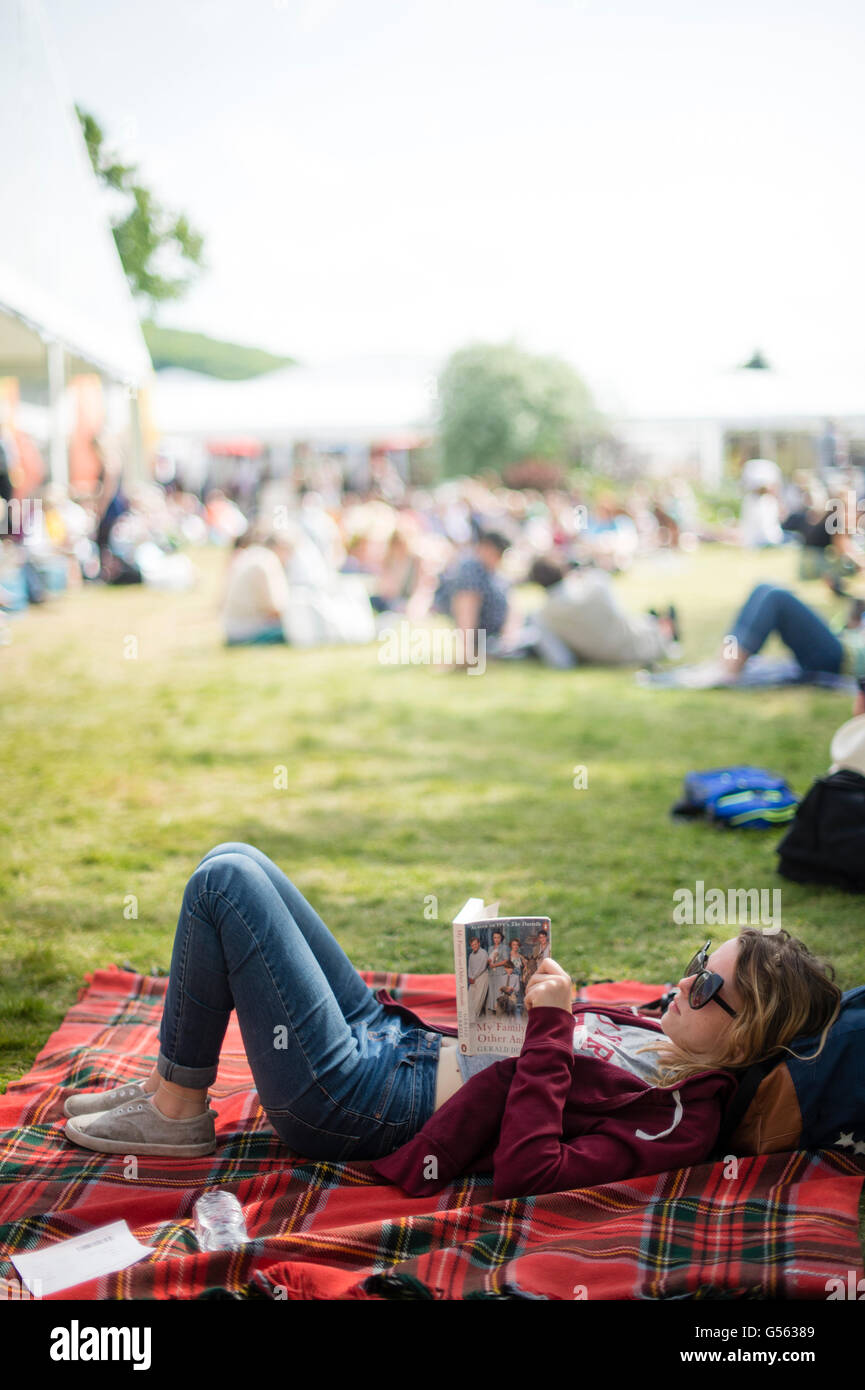 A young woman on the lawn reading her book at  the annual The Hay Festival of Literature and the Arts, 'the - Stock Image