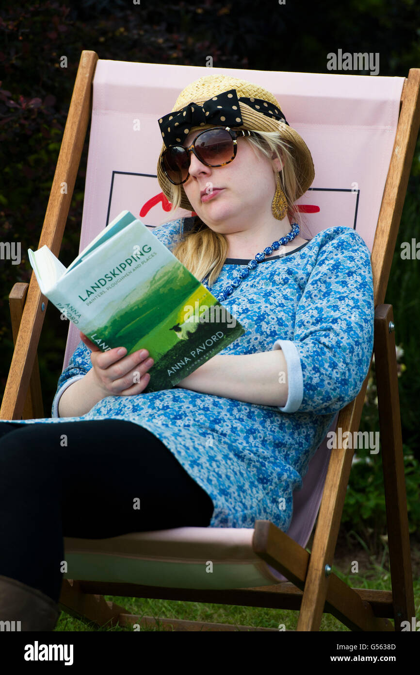 A young woman in a deckchair reading the book 'Landskipping' by Anna Pavord at the annual The Hay Festival - Stock Image