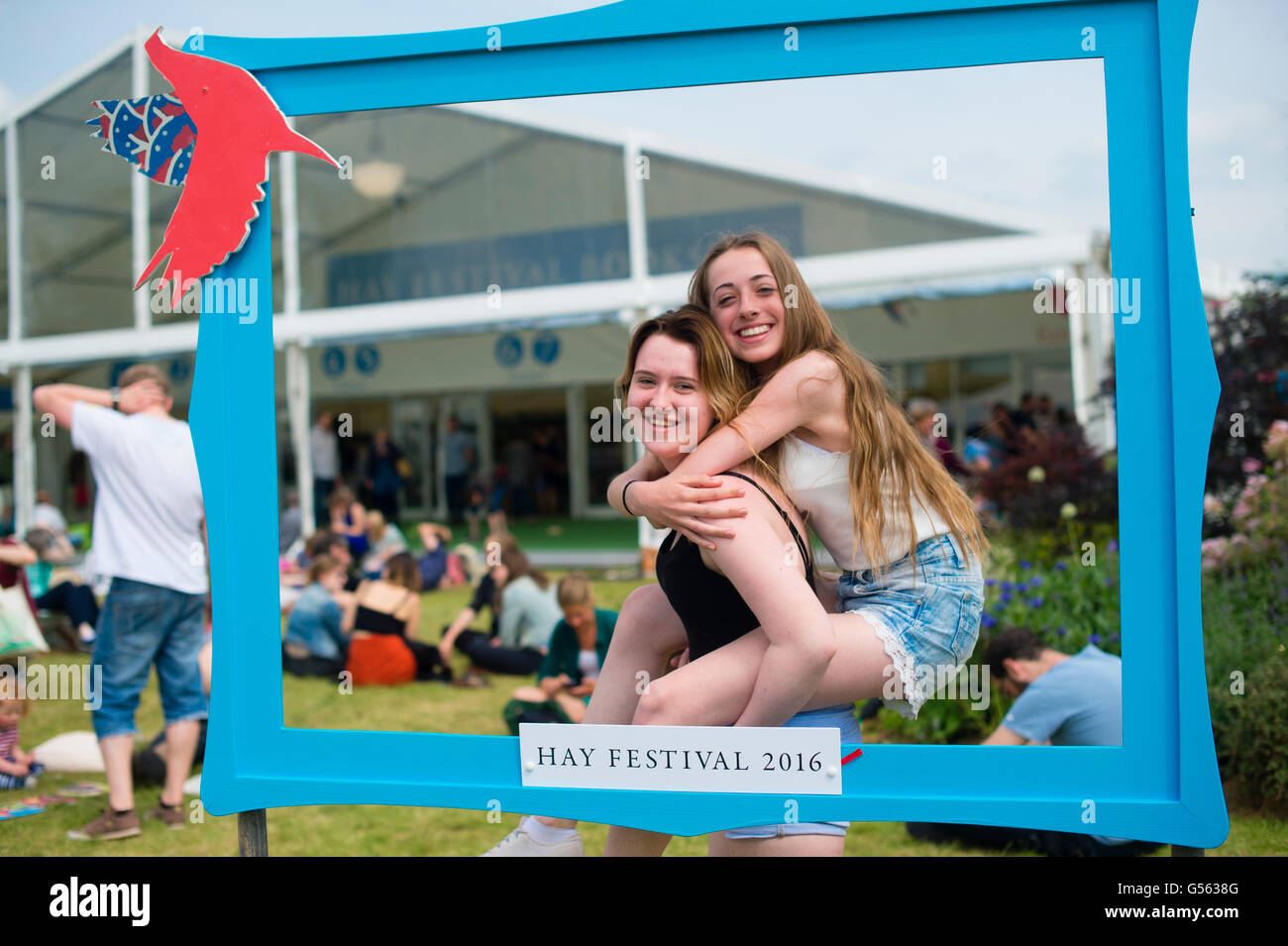 Two teenage girls posing for a photograph in a frame at  the annual The Hay Festival of Literature and the Arts, - Stock Image
