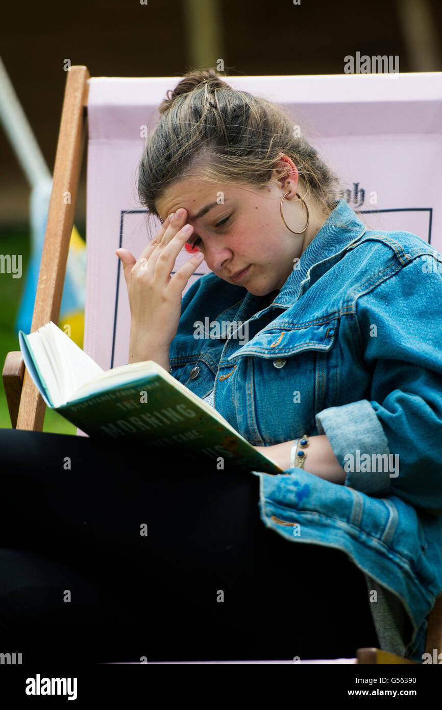 A young woman in a deckchair reading her book at the annual The Hay Festival of Literature and the Arts, 'the - Stock Image