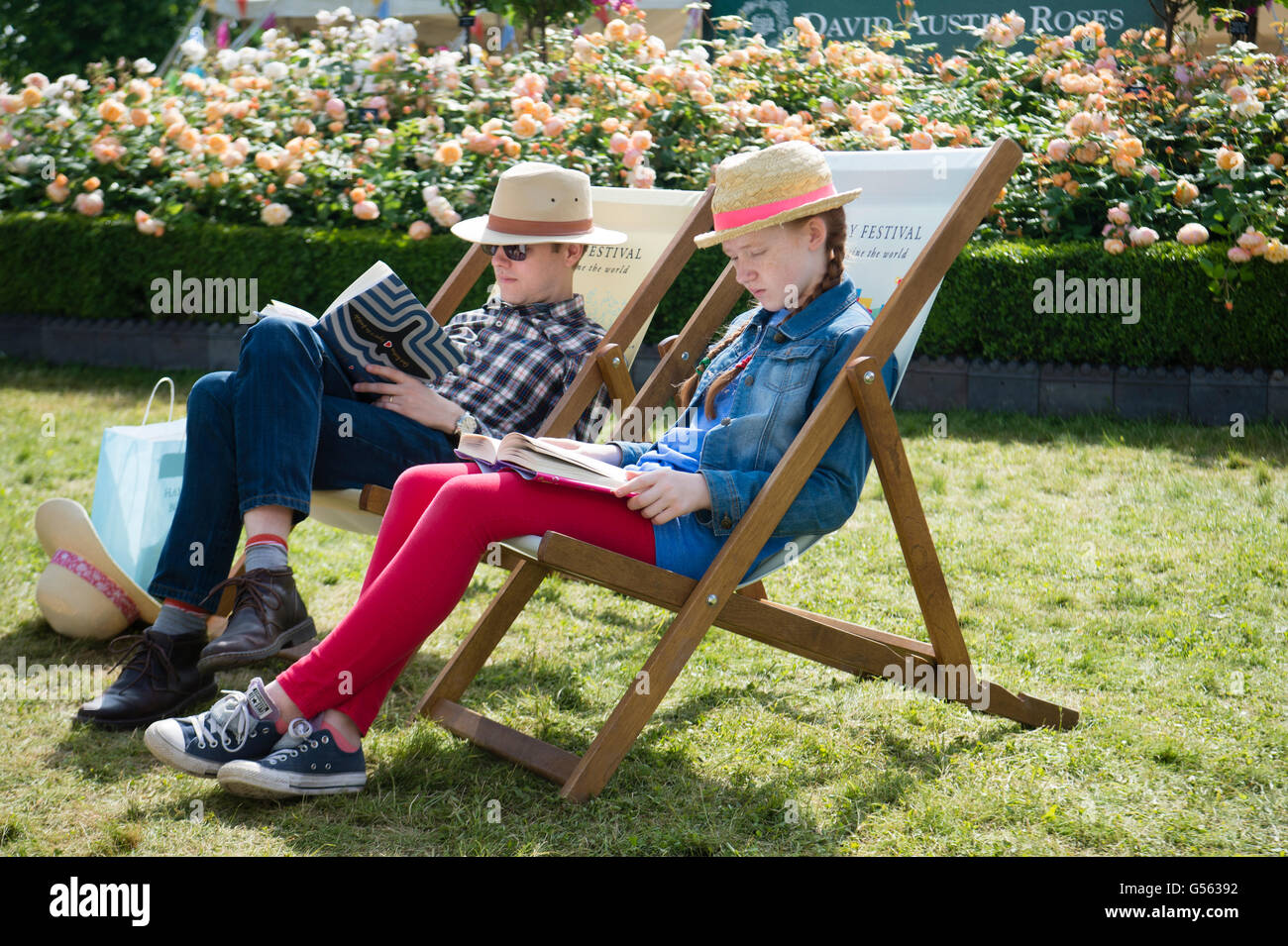 A couple, man and woman, sitting in deckchairs reading books in the warm sunshine a t  the annual The Hay Festival - Stock Image