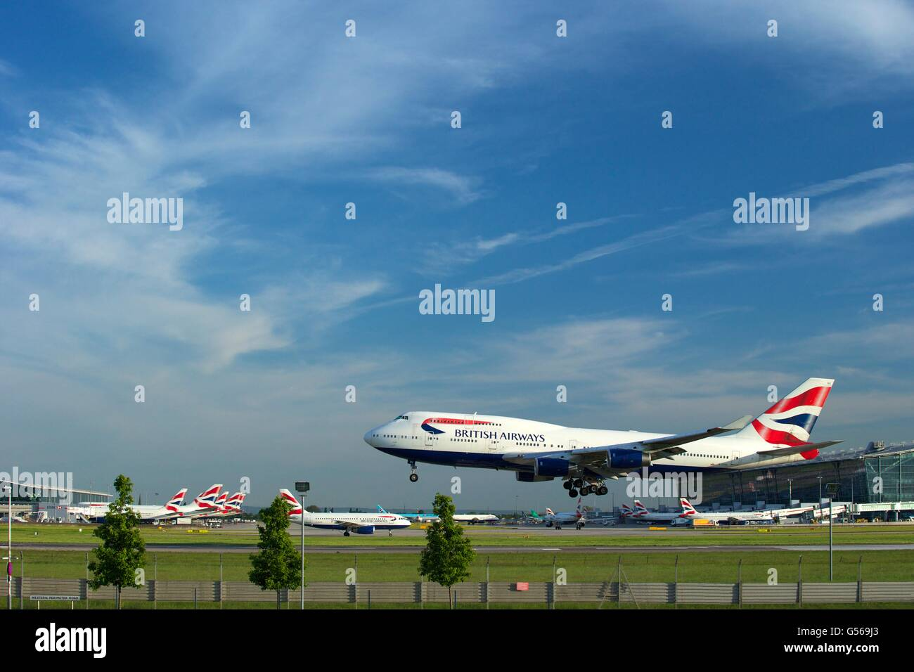 British AIrways flight landing at Heathrow Airport with Terminal 5 behind, London, England, UK, GB, - Stock Image