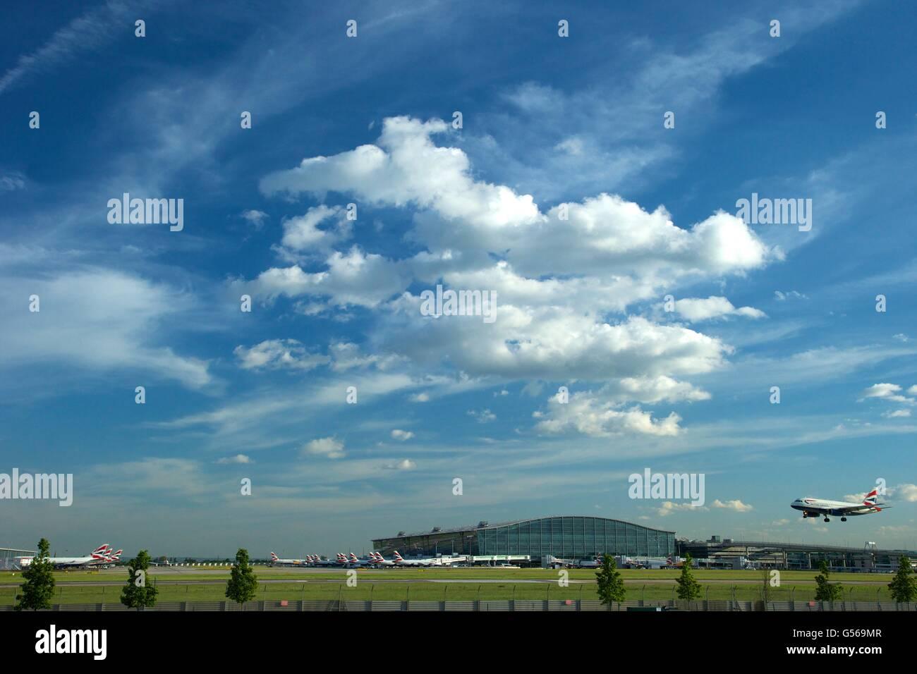British AIrways flight landing at Heathrow Airport with Terminal 5 behind, London, England, UK, GB, - Stock Image