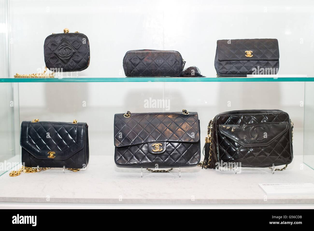 02b1497c1db4 THREE CHANEL BLACK QUILTED SATIN EVENING BAGS LATE 20TH CENTURY Comprising:  a square clutch with gold hardware, gold leather interior and gold chain ...