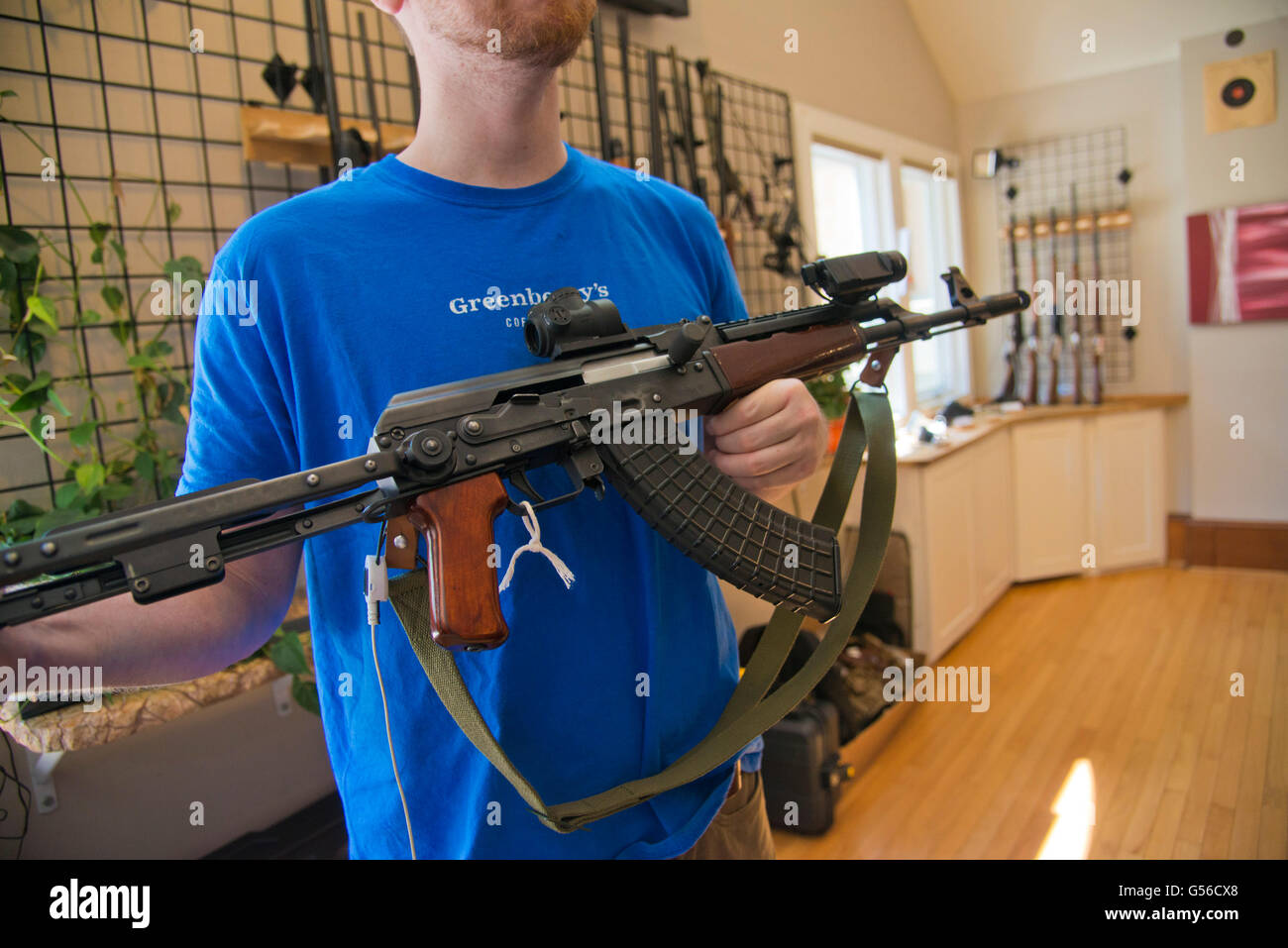 Falls Church, VA, June 19, 2016, USA--A gun owner holds the iconic AK-47 machine gun in a gun shop in Virginia. Stock Photo
