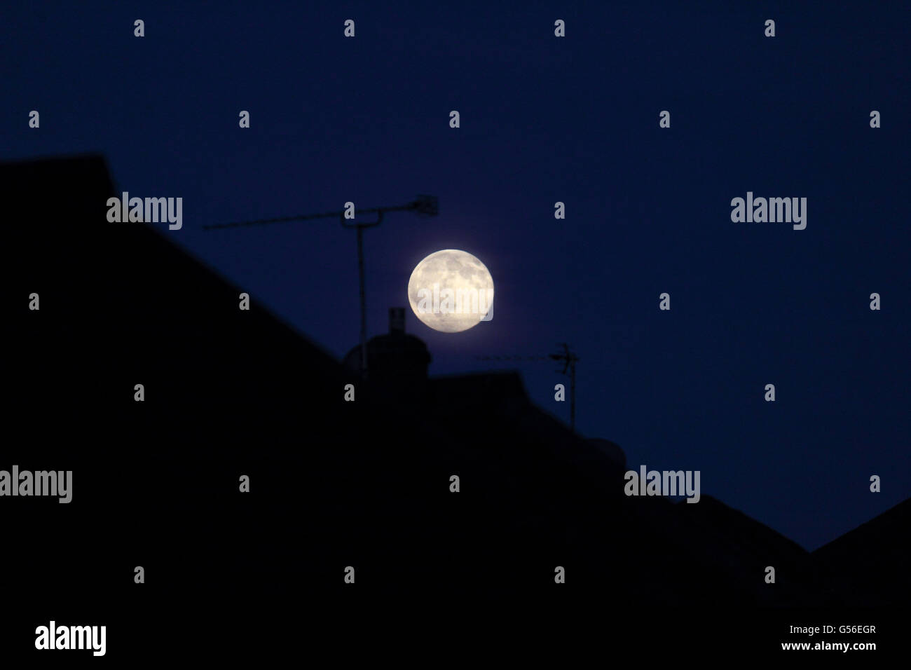 Epsom, Surrey, England, UK. 20th June 2016. The rising full or 'strawberry moon' on the evening of the summer - Stock Image