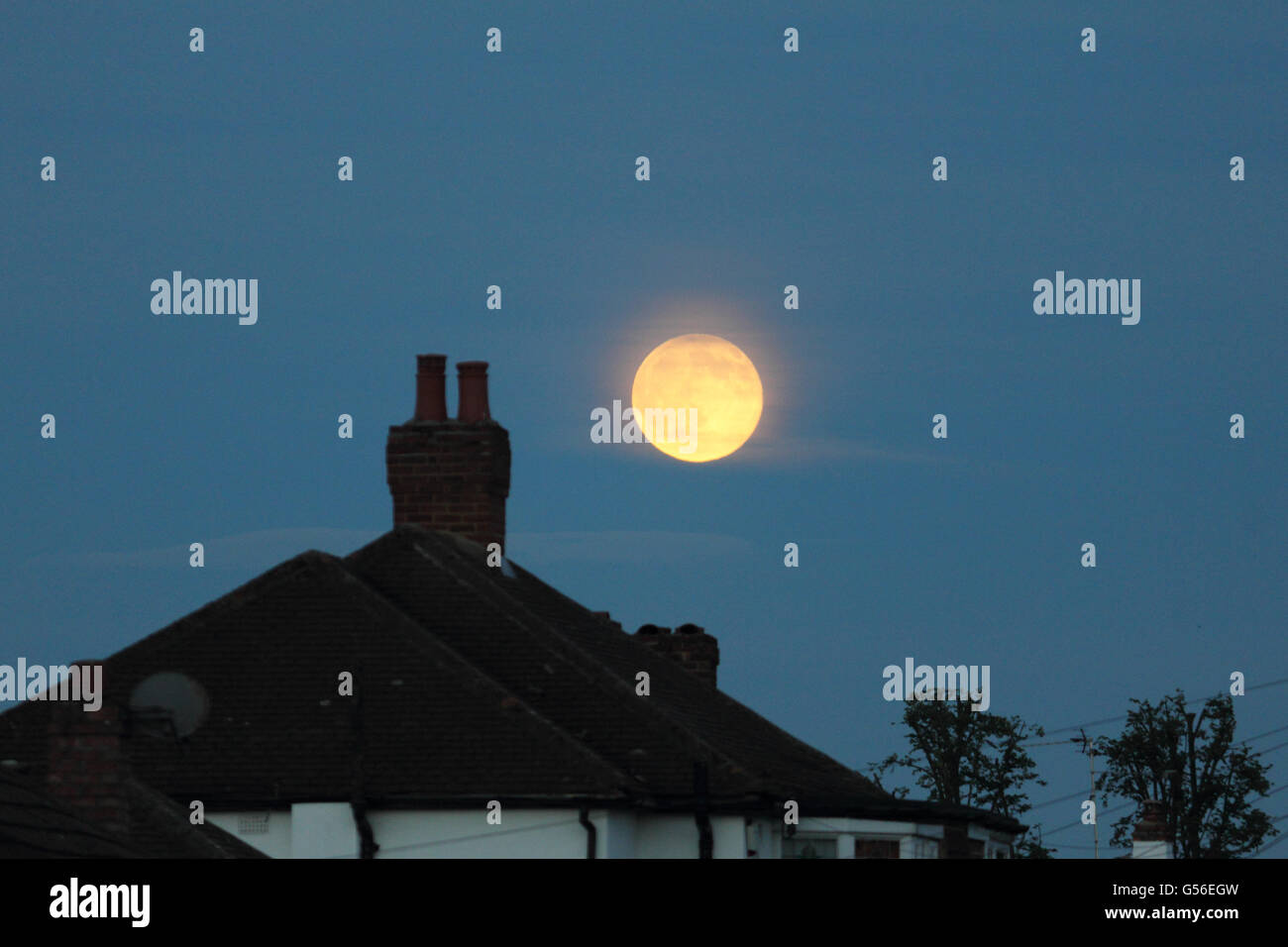Epsom, Surrey, England, UK. 20th June 2016. The orange glow over the roof tops of the rising full or 'strawberry - Stock Image