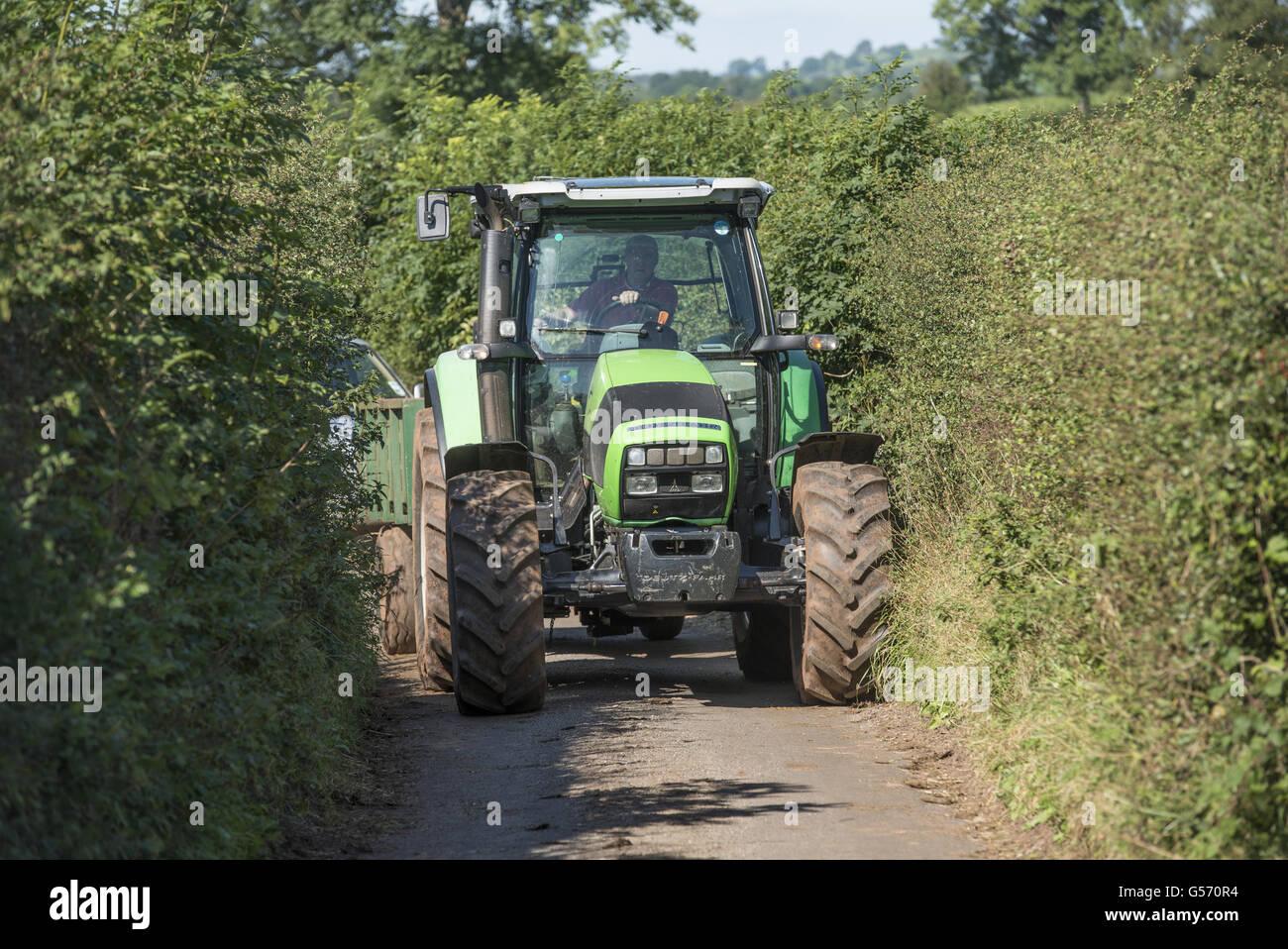 Deutz Fahr tractor driving along narrow country lane, Cumbria, England, September Stock Photo