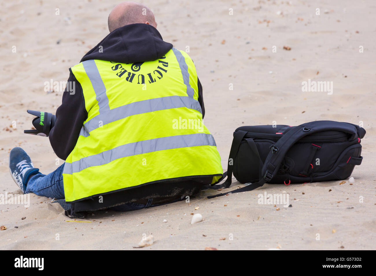 Photographer sitting on beach wearing hi vis vest at Bournemouth Wheels Festival in June - Stock Image