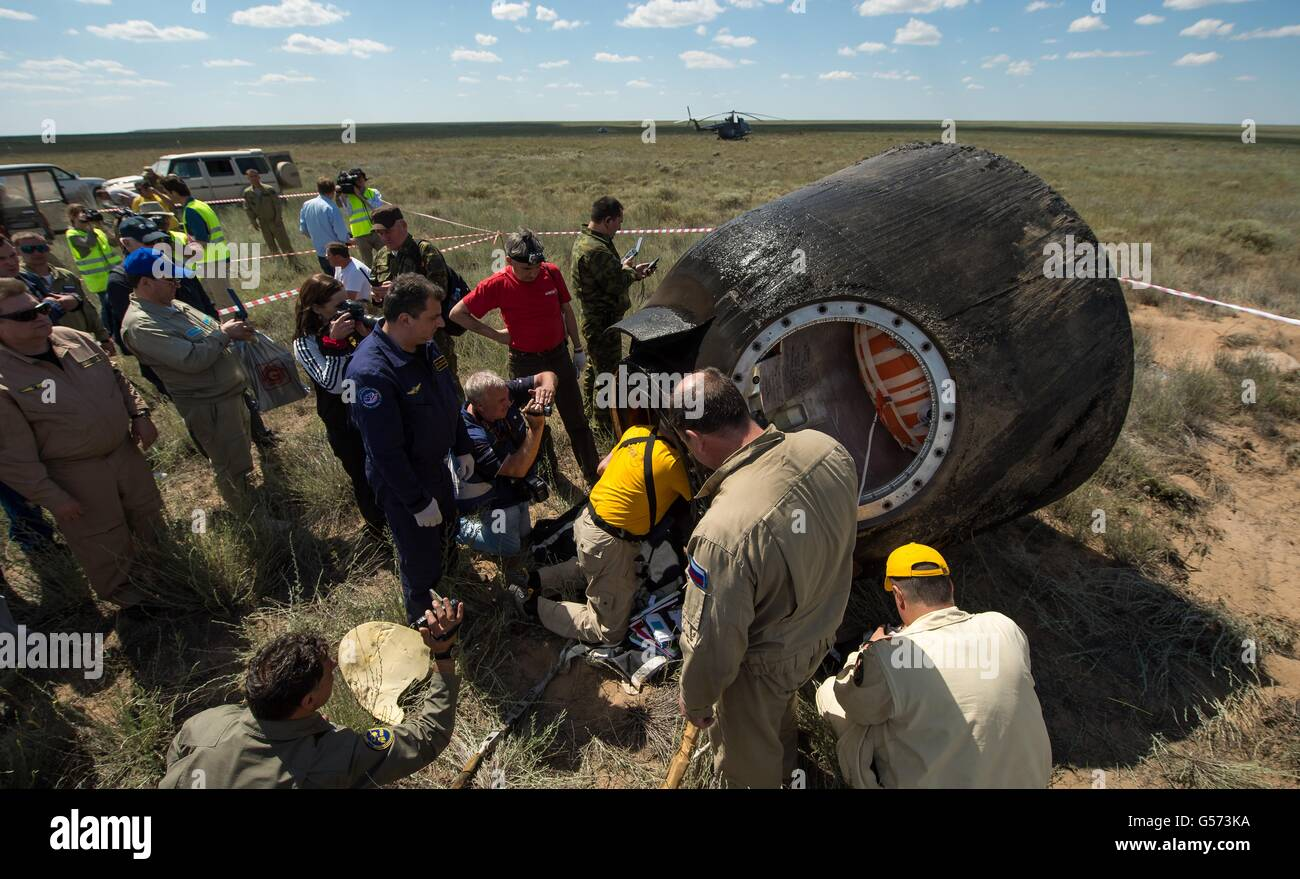 Russian supporter personnel gather around the Soyuz TMA-19M spacecraft to assist the International Space Station - Stock Image