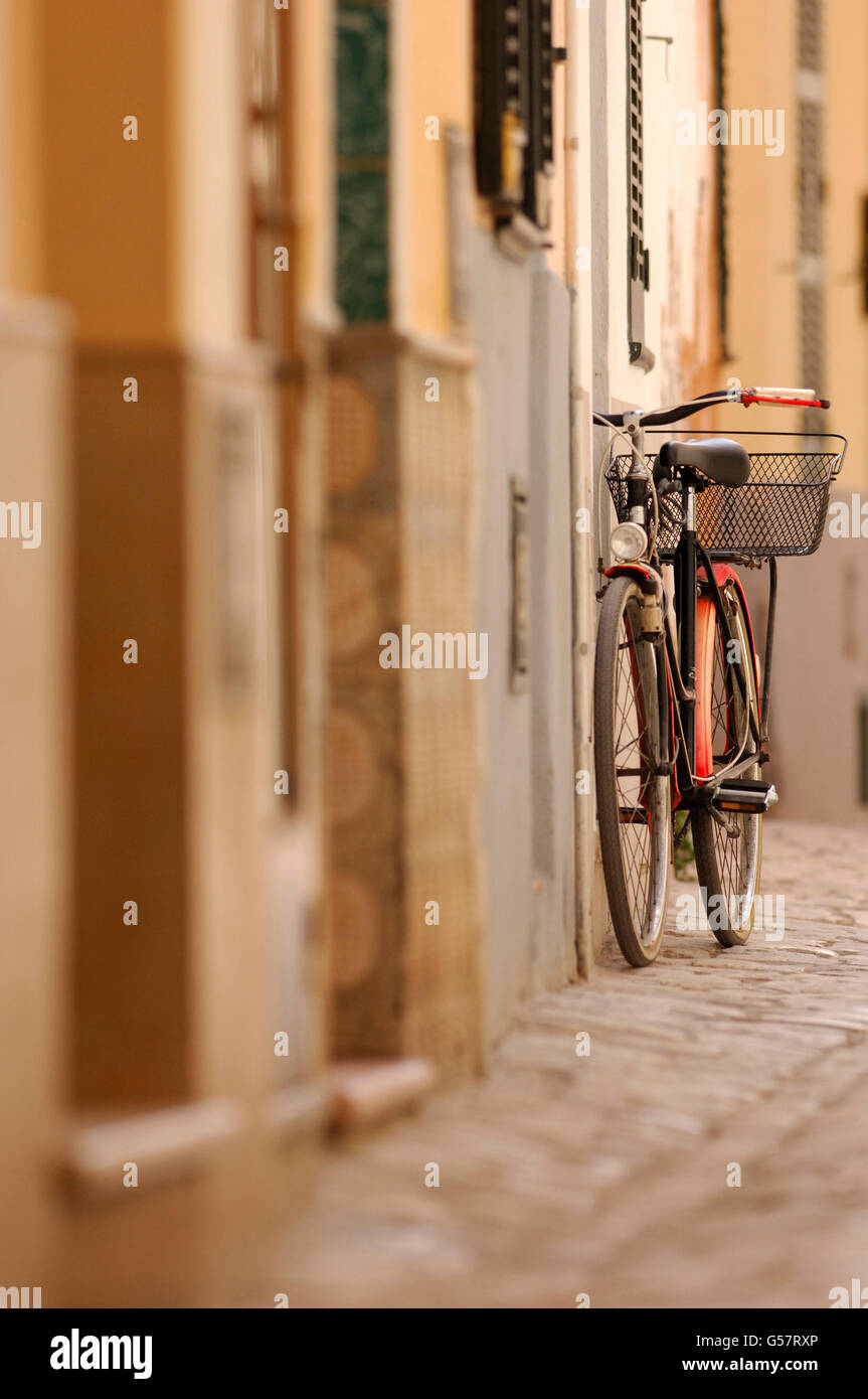 Old Bike with red mudguards and basket leaning up against wall on a cobbled street Stock Photo