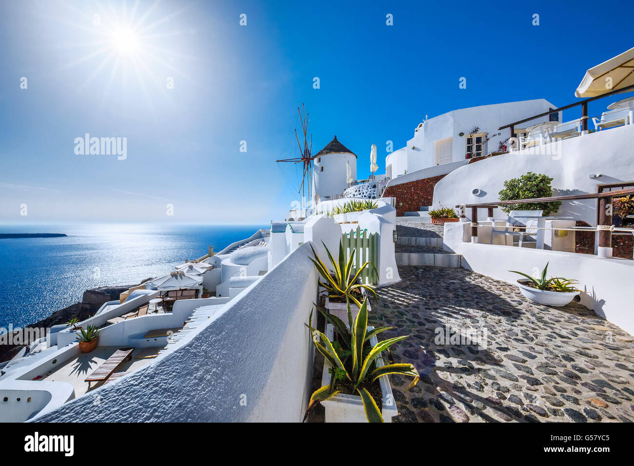 Oia village with sun, Santorini island, Greece - Stock Image