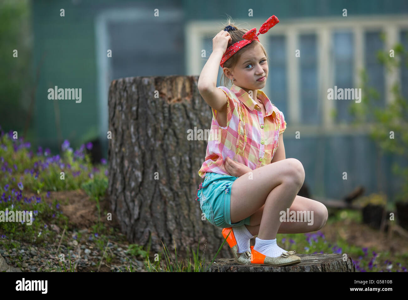 Puzzled little girl sitting near farm house. - Stock Image
