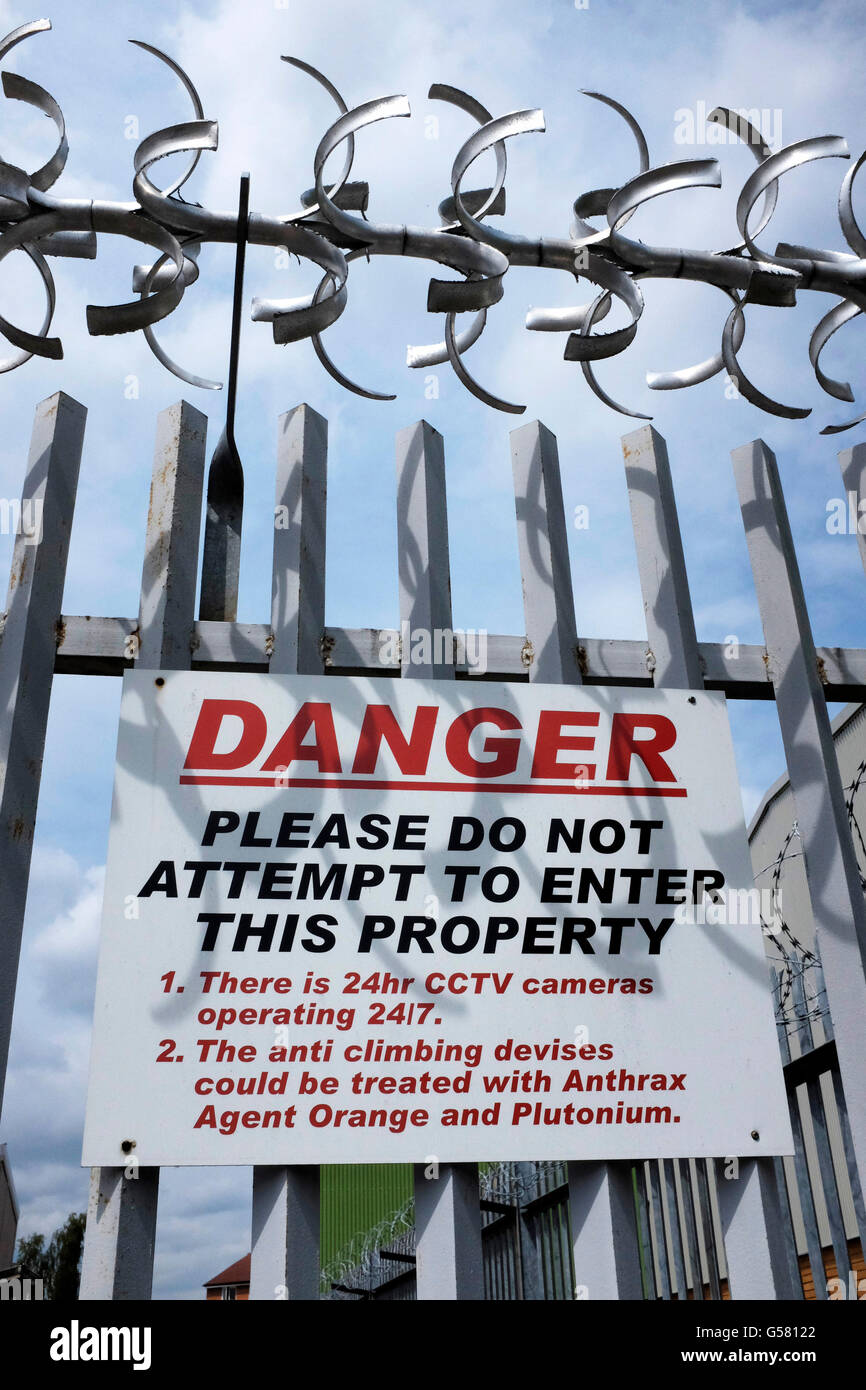 Alarming danger notice on a security fence outside an industrial estate in Perivale, London. - Stock Image