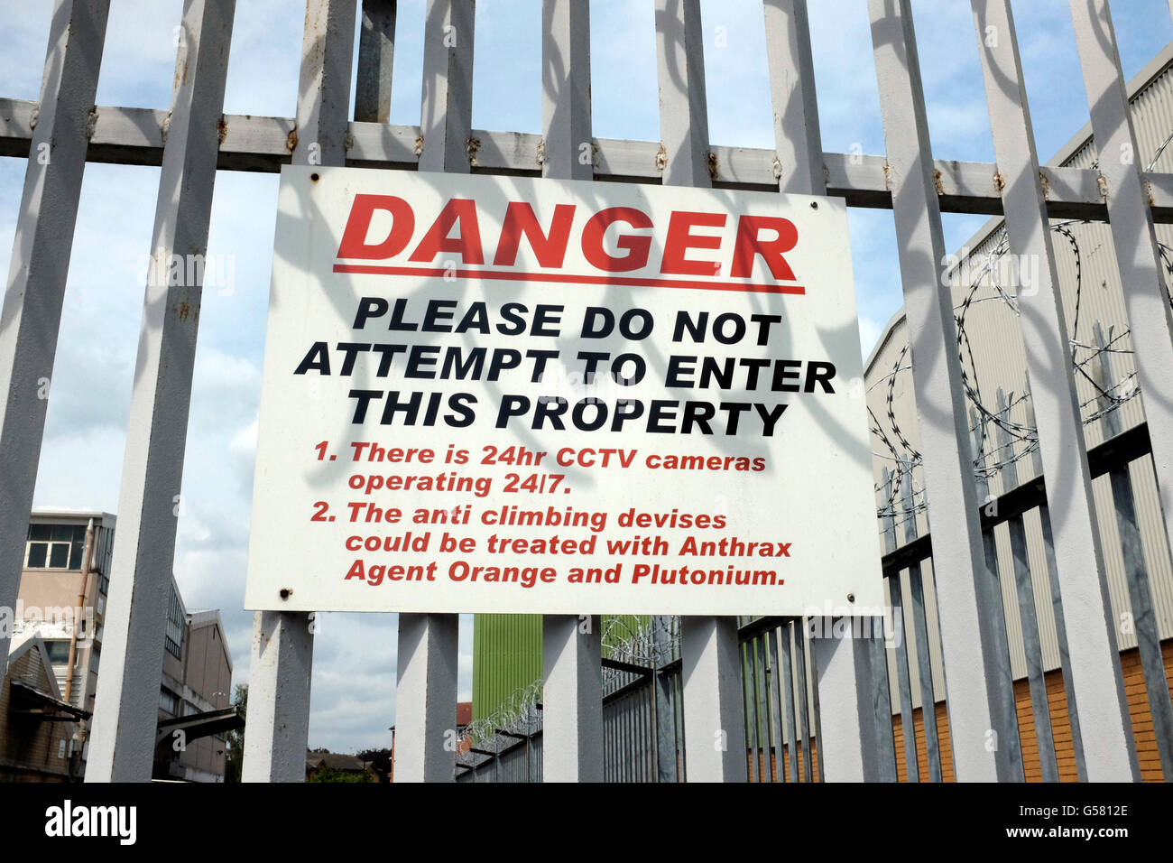 Warning sign outside an industrial estate in Perivale London stating it could that be protected by anthrax and agent - Stock Image