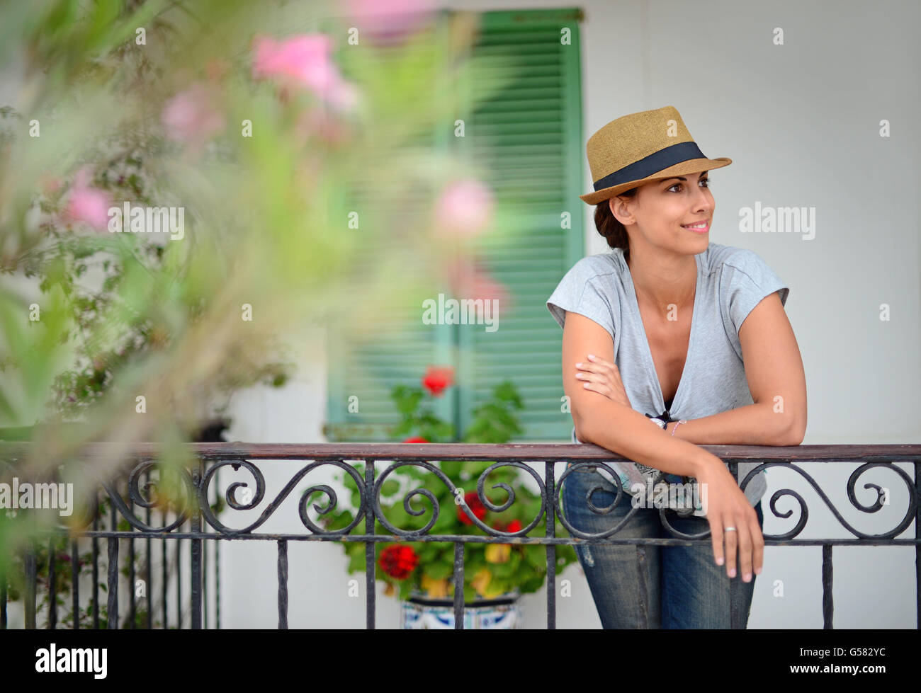 Attractive young woman poses in front of traditional house, Ibiza, Balearic Islands, Spain - Stock Image
