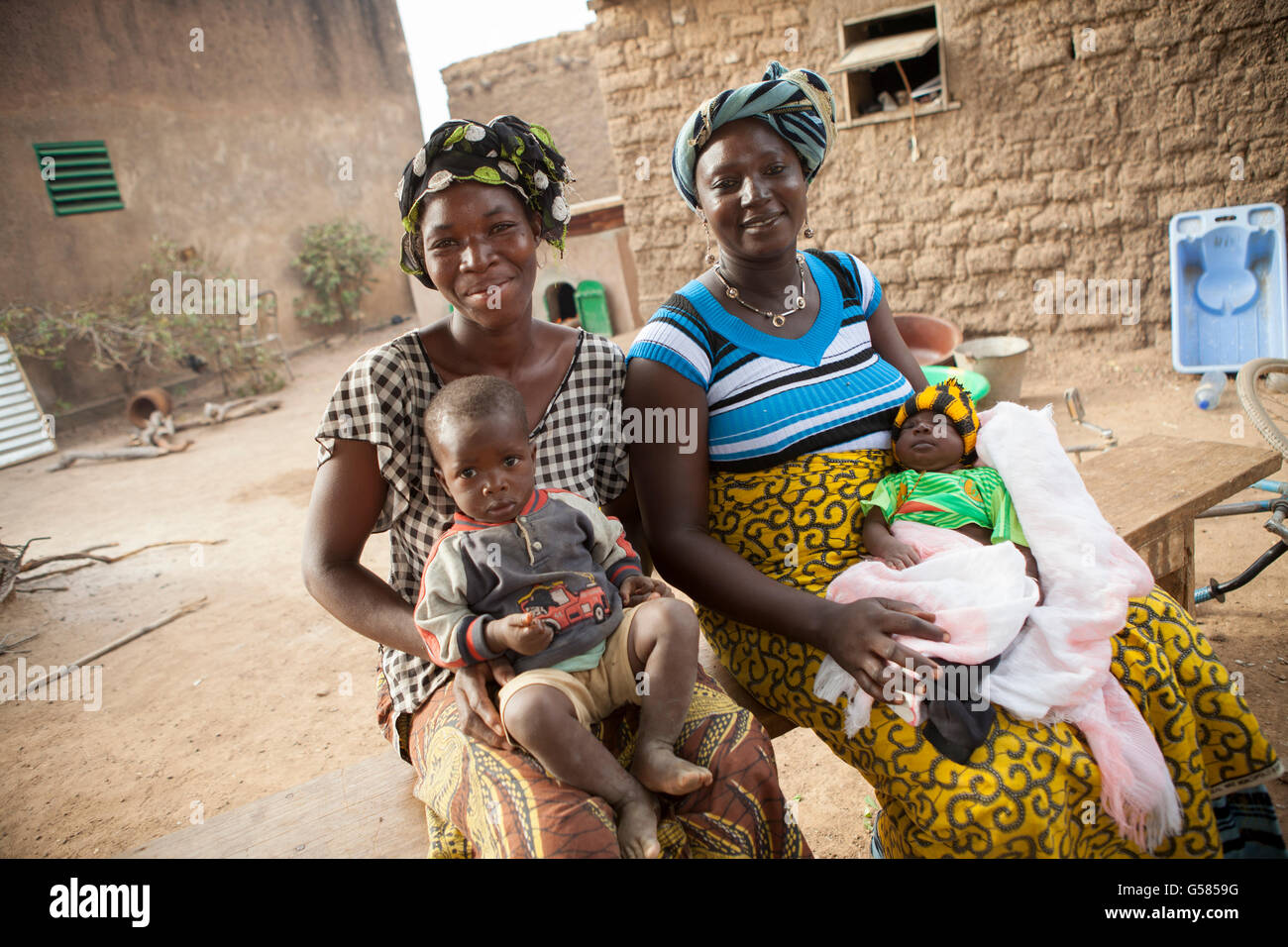 Two women stand together with their children in Niassan Village, Burkina Faso. Stock Photo