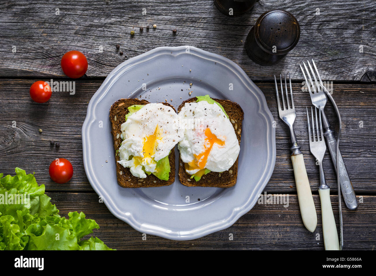 Avocado poached egg toasts on plate on dark rustic wooden background, overhead view. Healthy breakfast, lunch or - Stock Image
