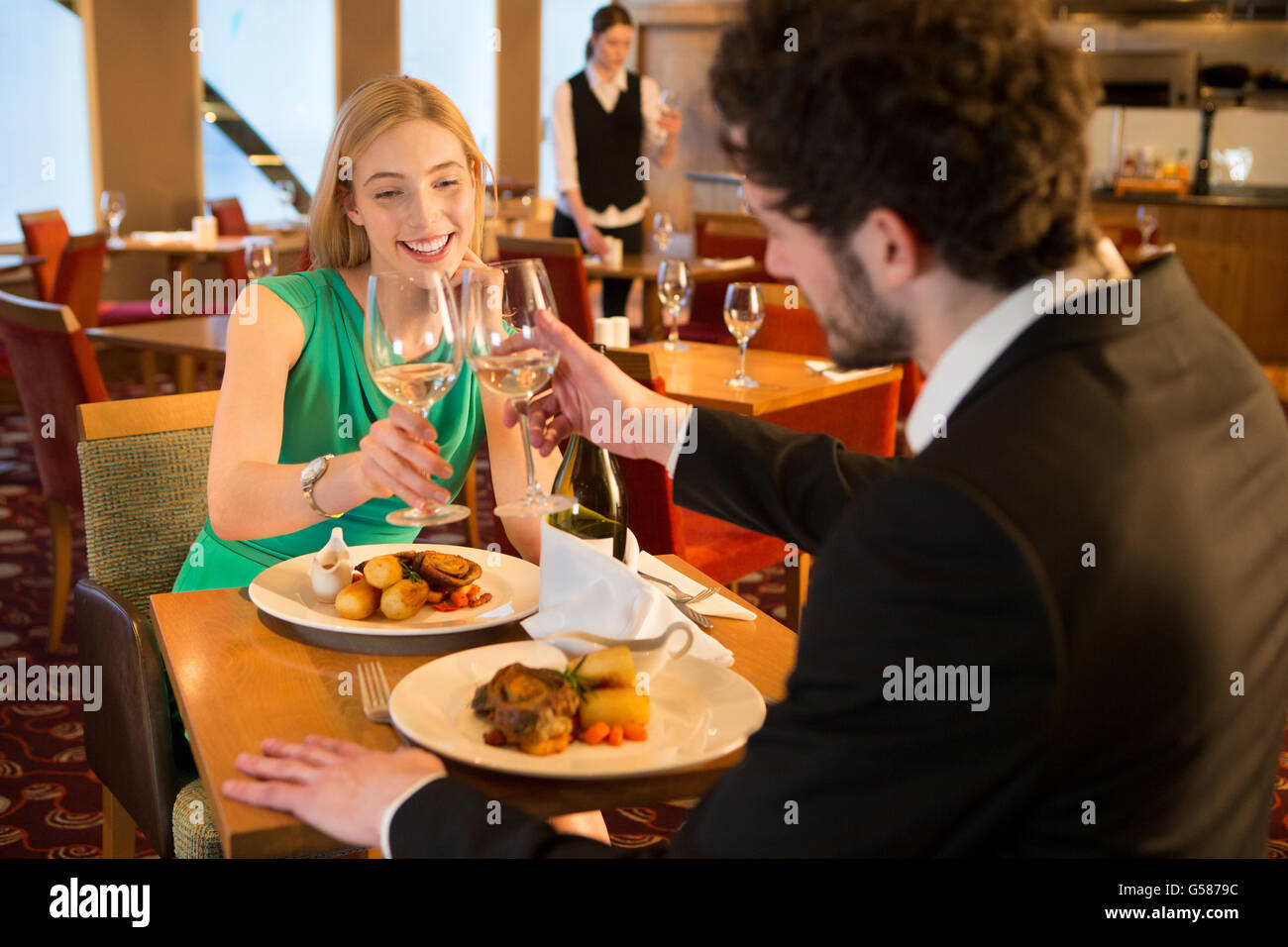 Young couple toasting their glasses of champagne over a meal in a restaurant. - Stock Image