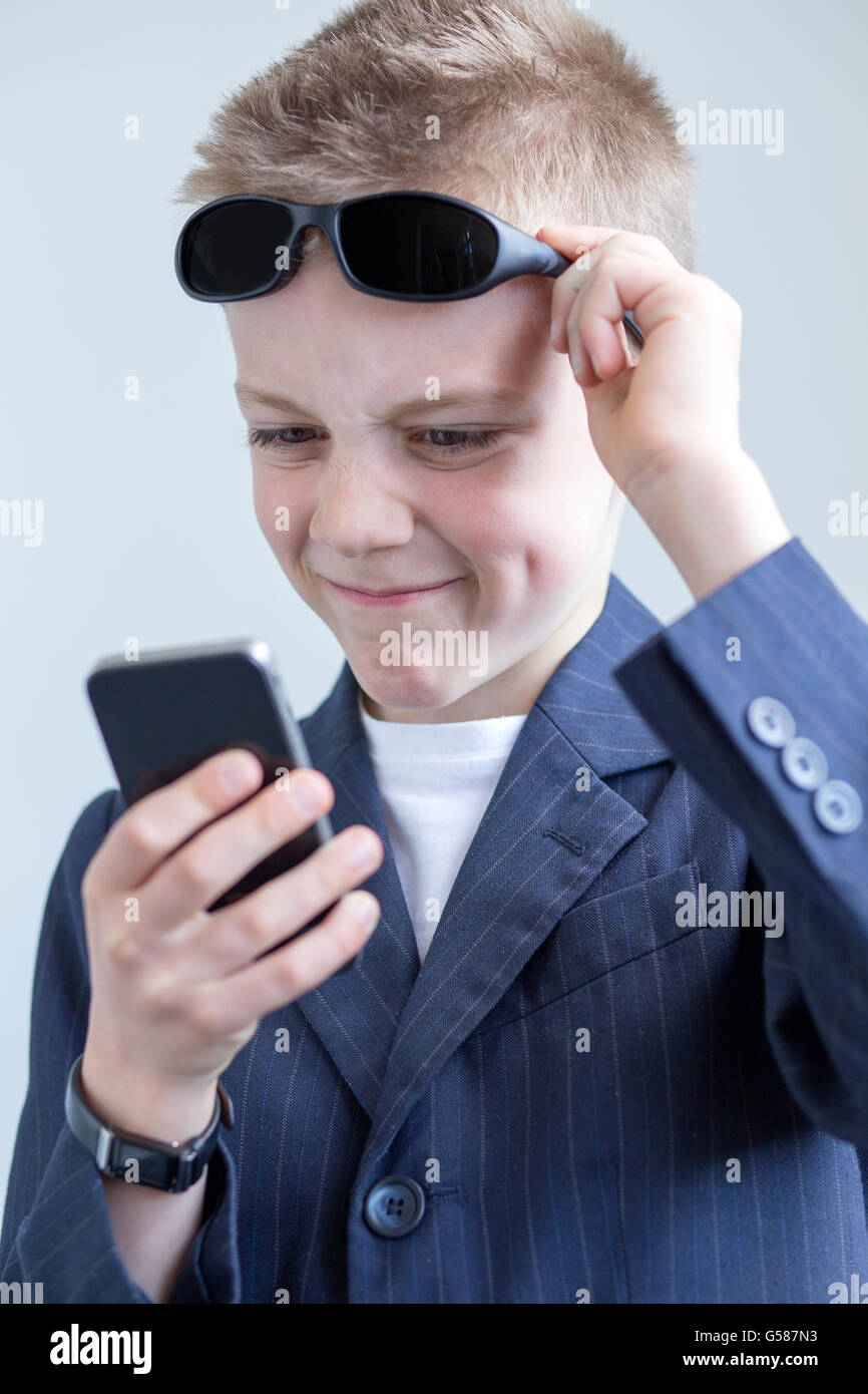 Young boy dressed up as a spy. He is looking at a smartphkone and pulling a funny face with his glasses being held - Stock Image