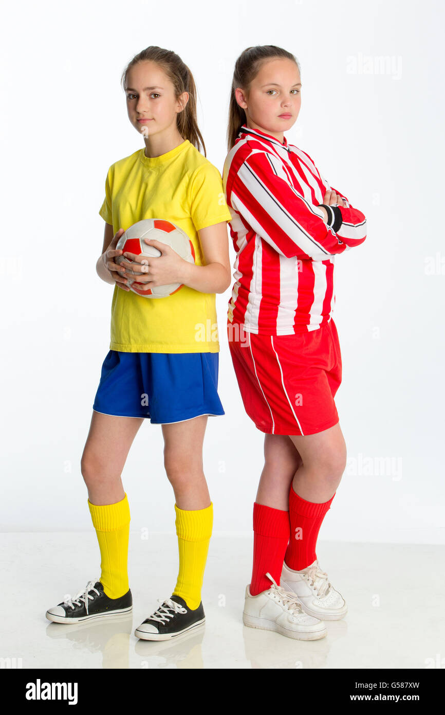 Football team captains looking competitive. They are standing back to back against a white background whilst looking - Stock Image