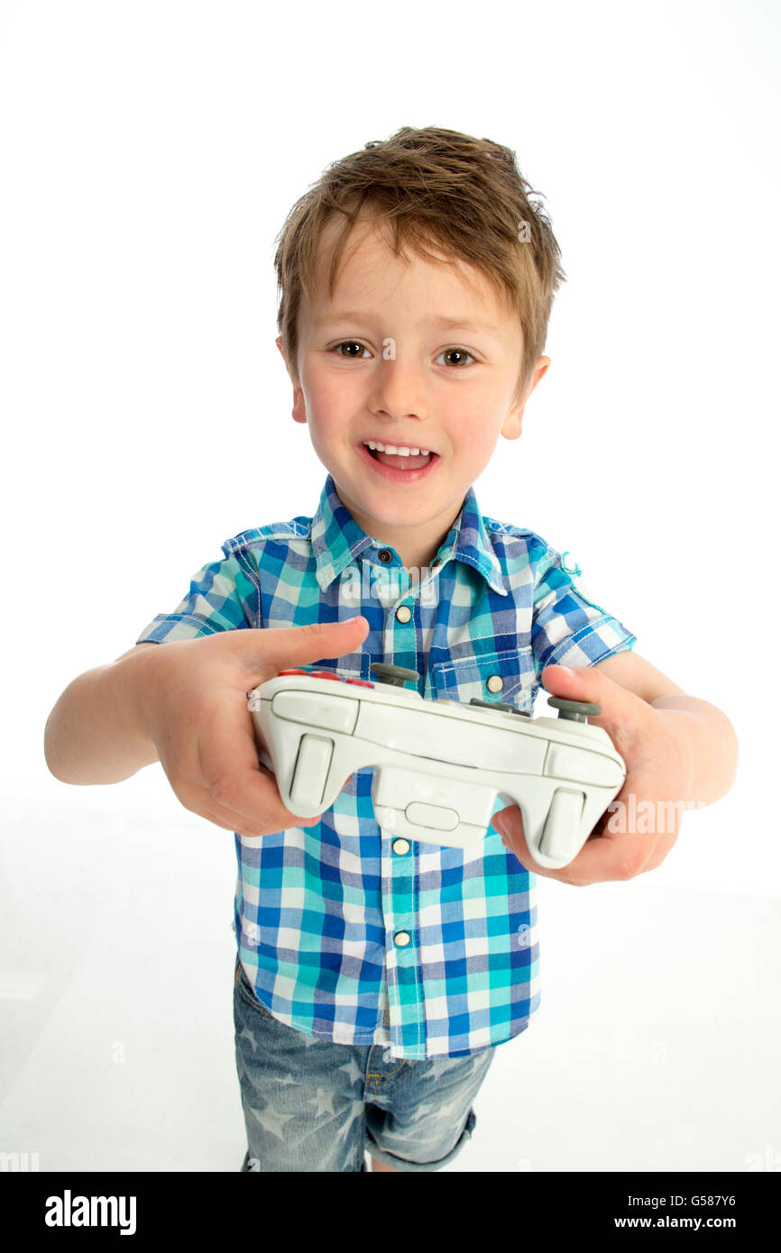 Young boy with a video game controller. He is standing against a white background. - Stock Image