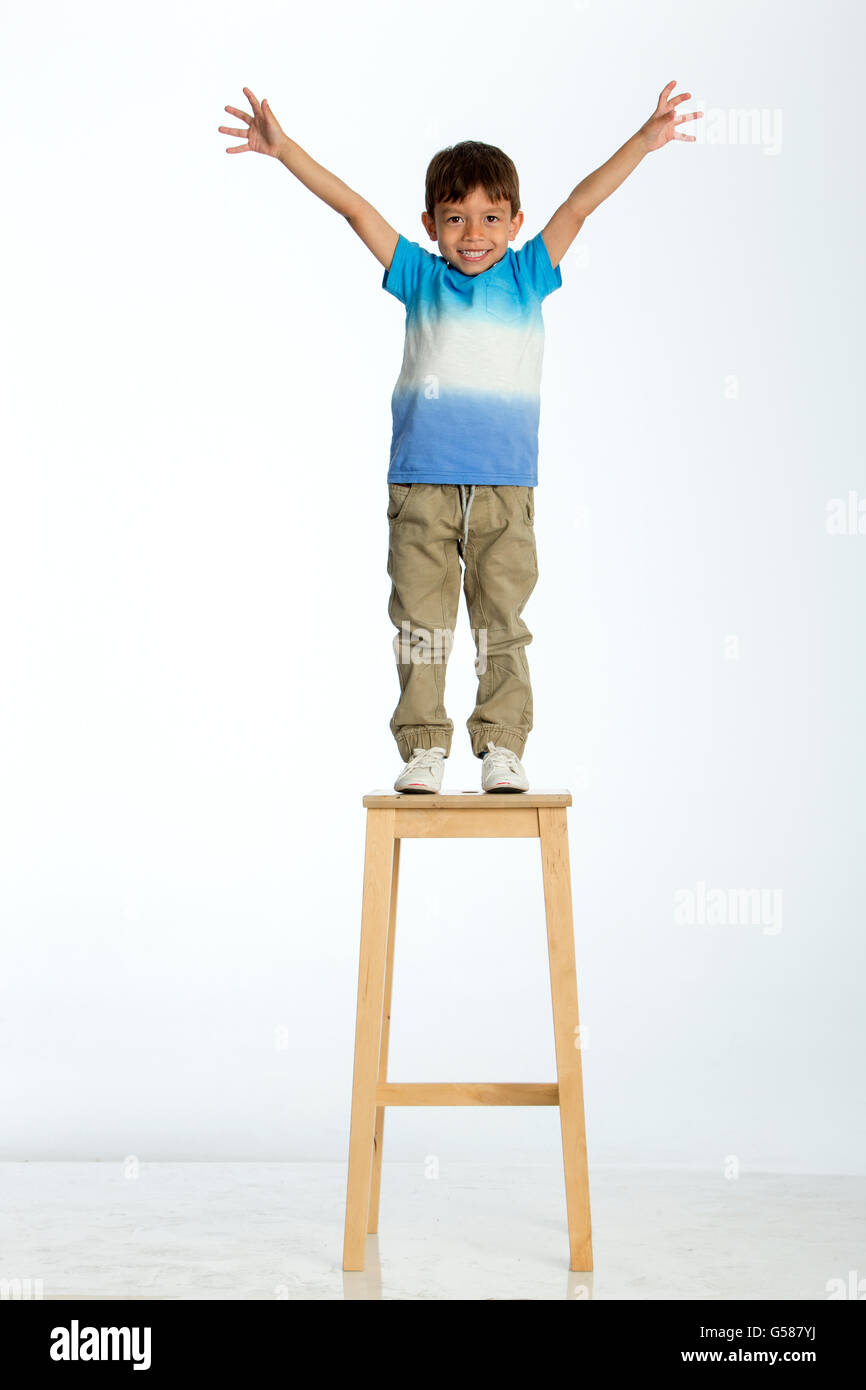 Little boy standing on a high stool with his arms out stretched. He is against a white background. - Stock Image