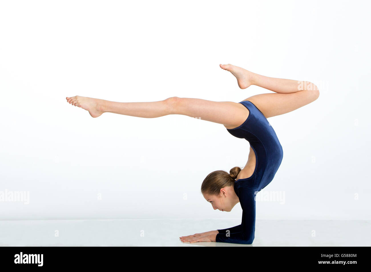 Female gymnast balancing in a pose on her arms against a white background. - Stock Image