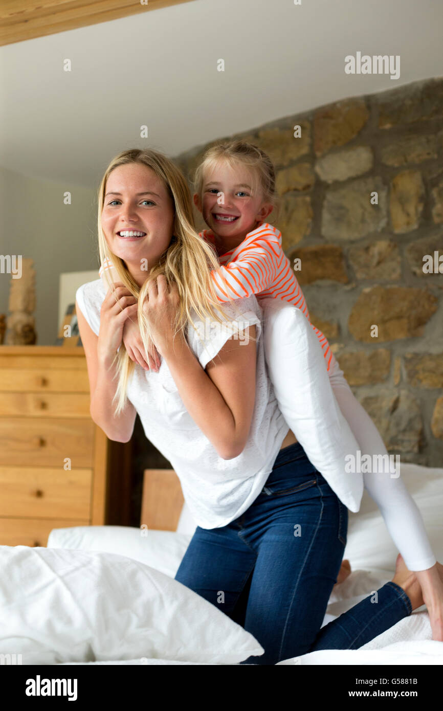 Mother and daughter playing on a bed at home, smiling for the camera - Stock Image