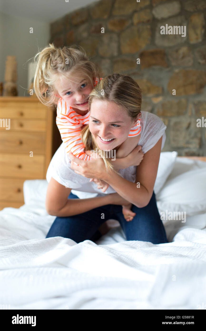 Mother and daughter playing on a bed at home - Stock Image