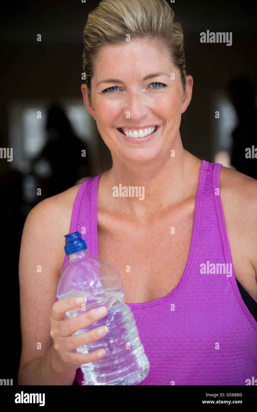 Portrait of a mature woman with a water bottle. She looks ready to do exercise. - Stock Image