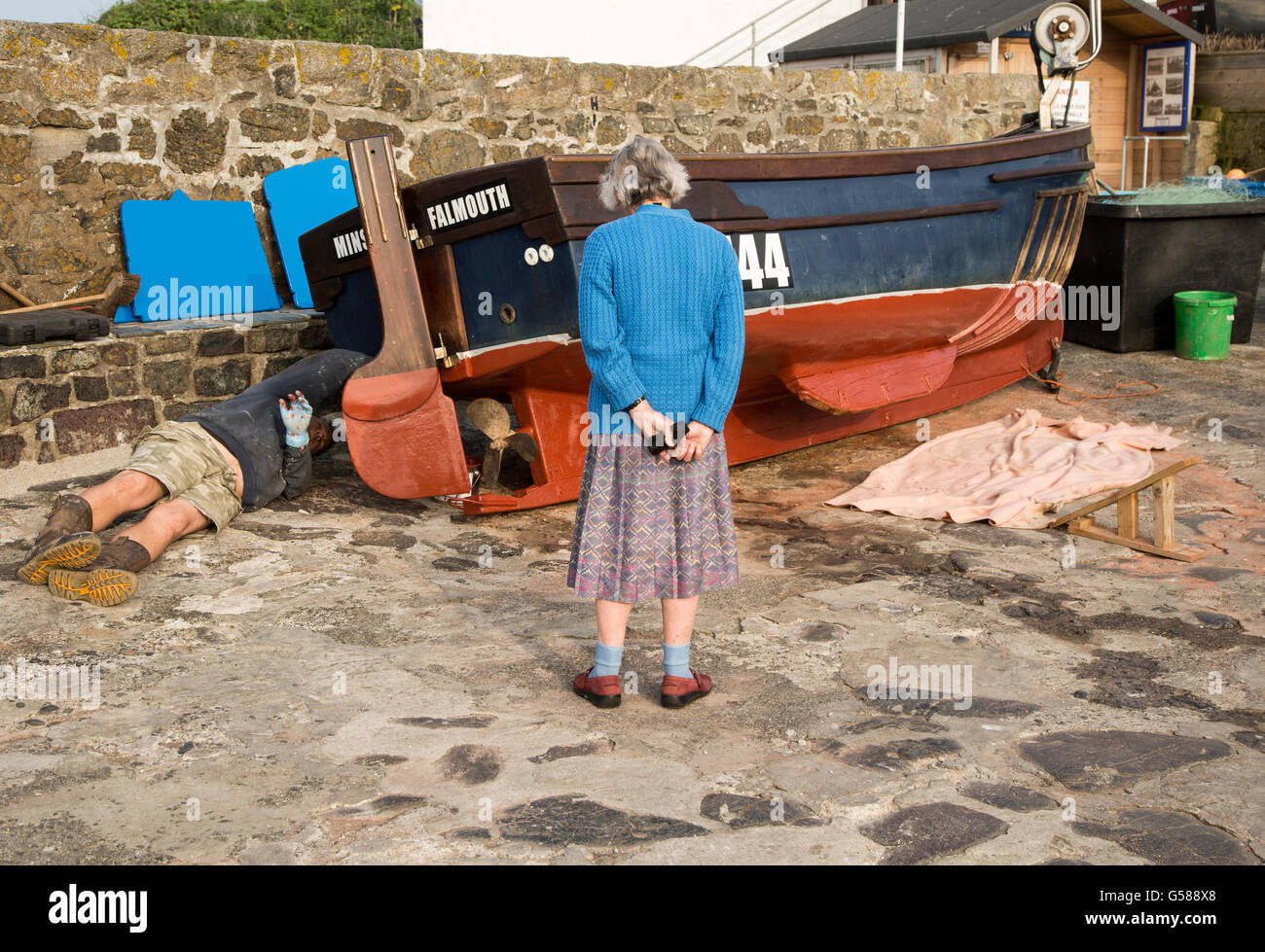 Man painting small fishing boat watched by an elderly woman presumably his mother, Coverack, Cornwall, England, - Stock Image