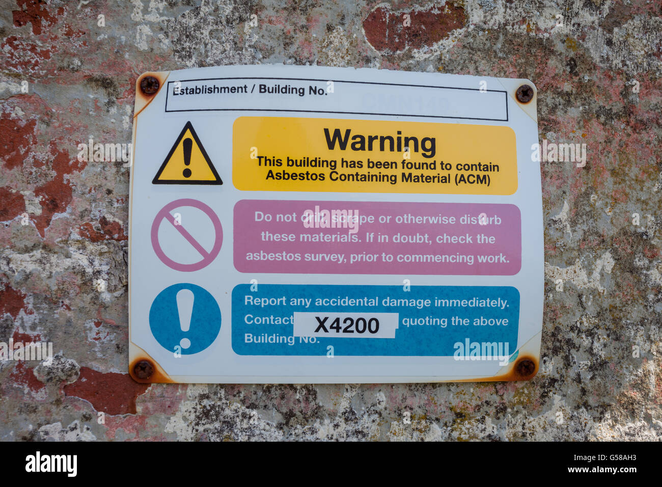 Sign on the exterior wall of a building showing a warning that the building contains asbestos. - Stock Image