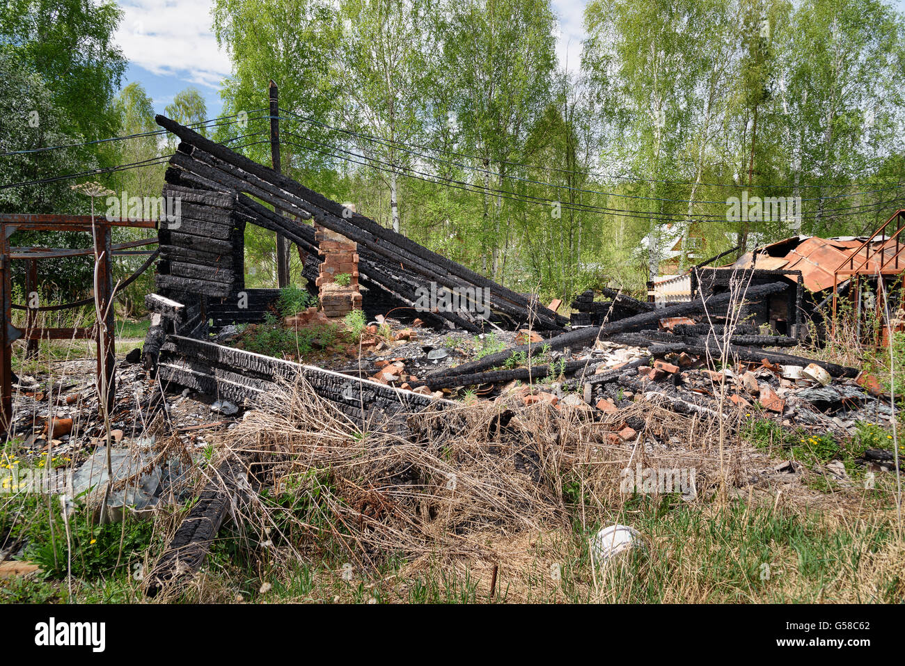 Remains of burned down house in the village - Stock Image