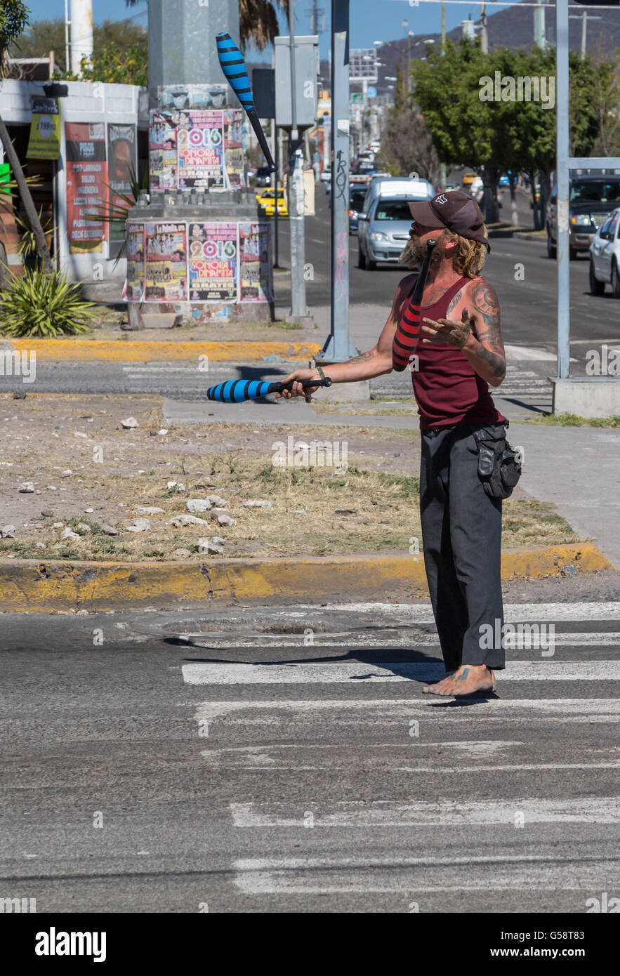 Street entertainer juggling during a stop in traffic in Santiago de Queretaro, Queretaro, Mexico - Stock Image