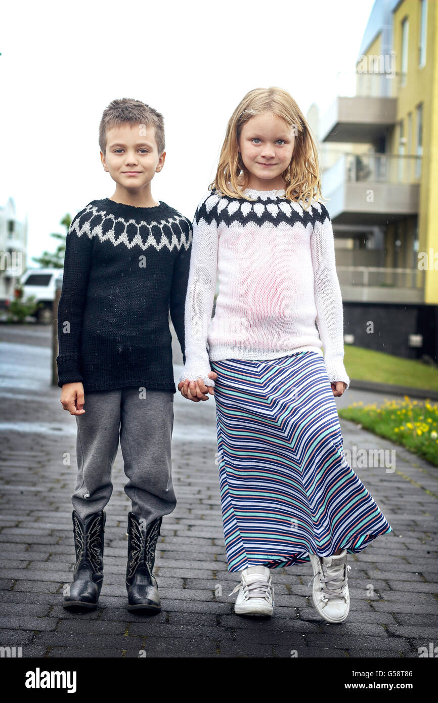 A boy and a girl holding hands - Stock Image