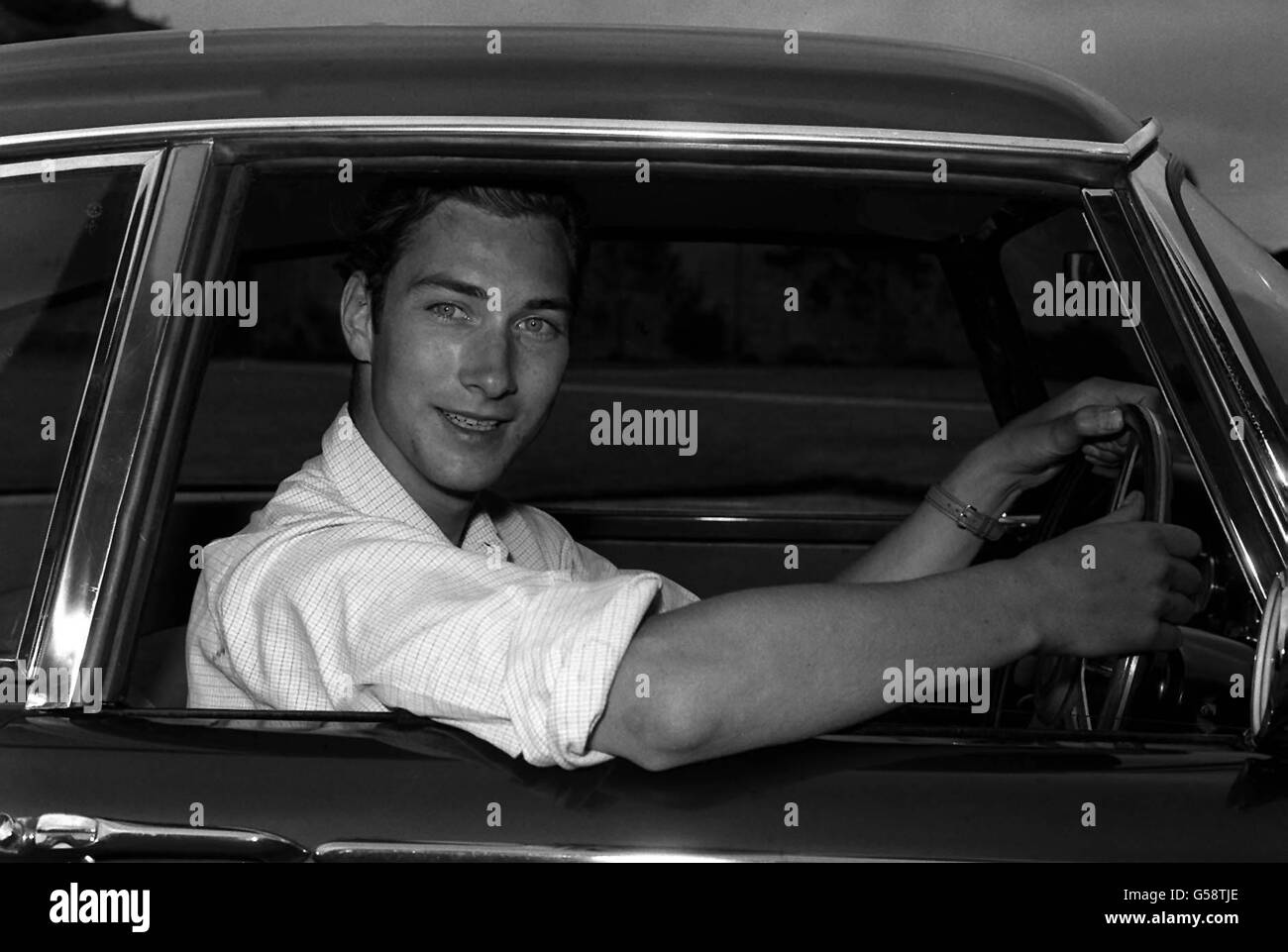 1962: Prince William of Gloucester, who loves driving, pictured at the wheel of his car at his home, Barnwell Manor, near Peterborough. The Prince, elder son of the Duke and Duchess of Gloucester, celebrates his 21st birthday on December 18th. He is 7th in line of succession to the throne. (Killed in air accident 28/8/72). Stock Photo