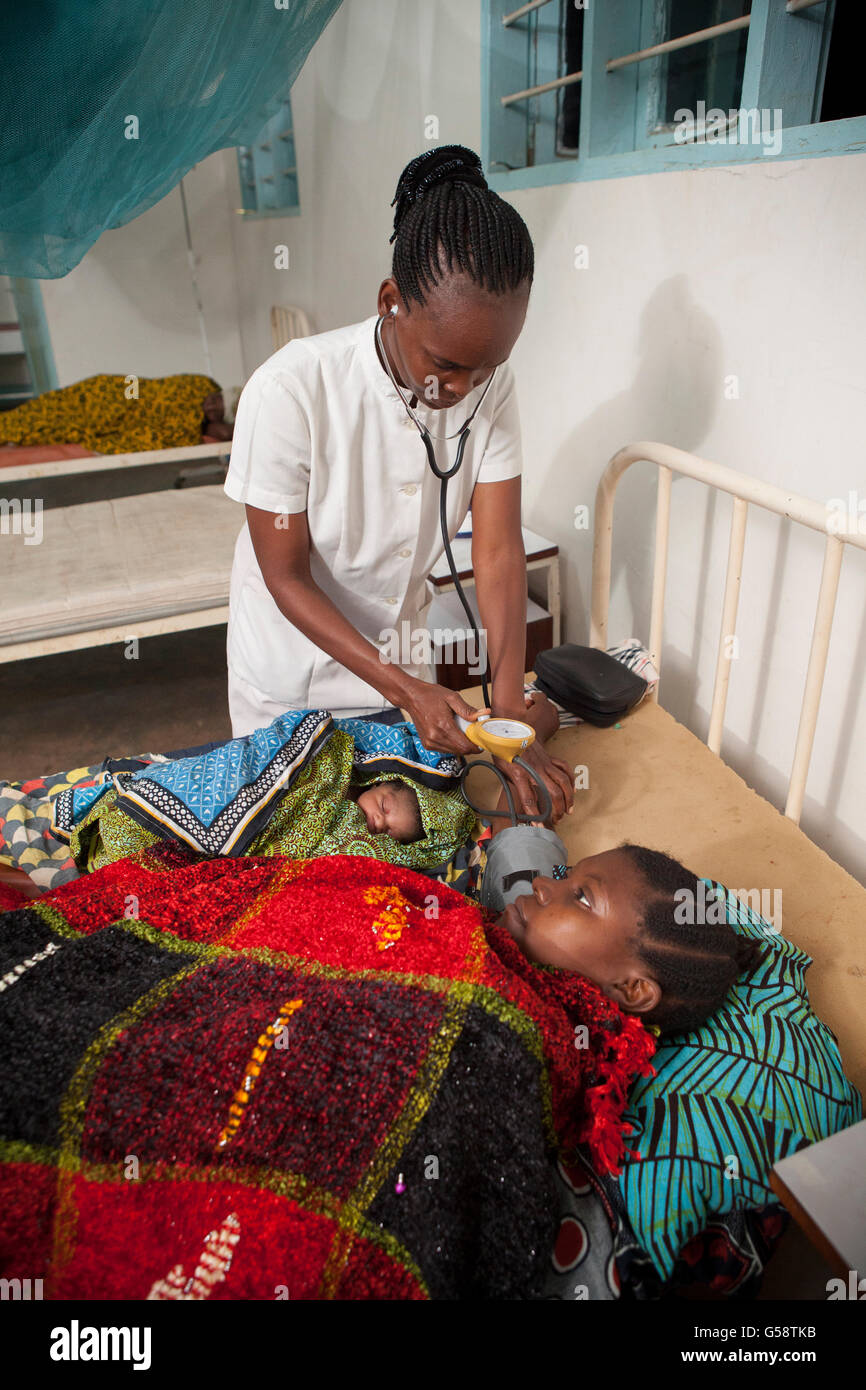 A nurse attends to a patient and her newborn baby in Kigoma Region, Tanzania. - Stock Image